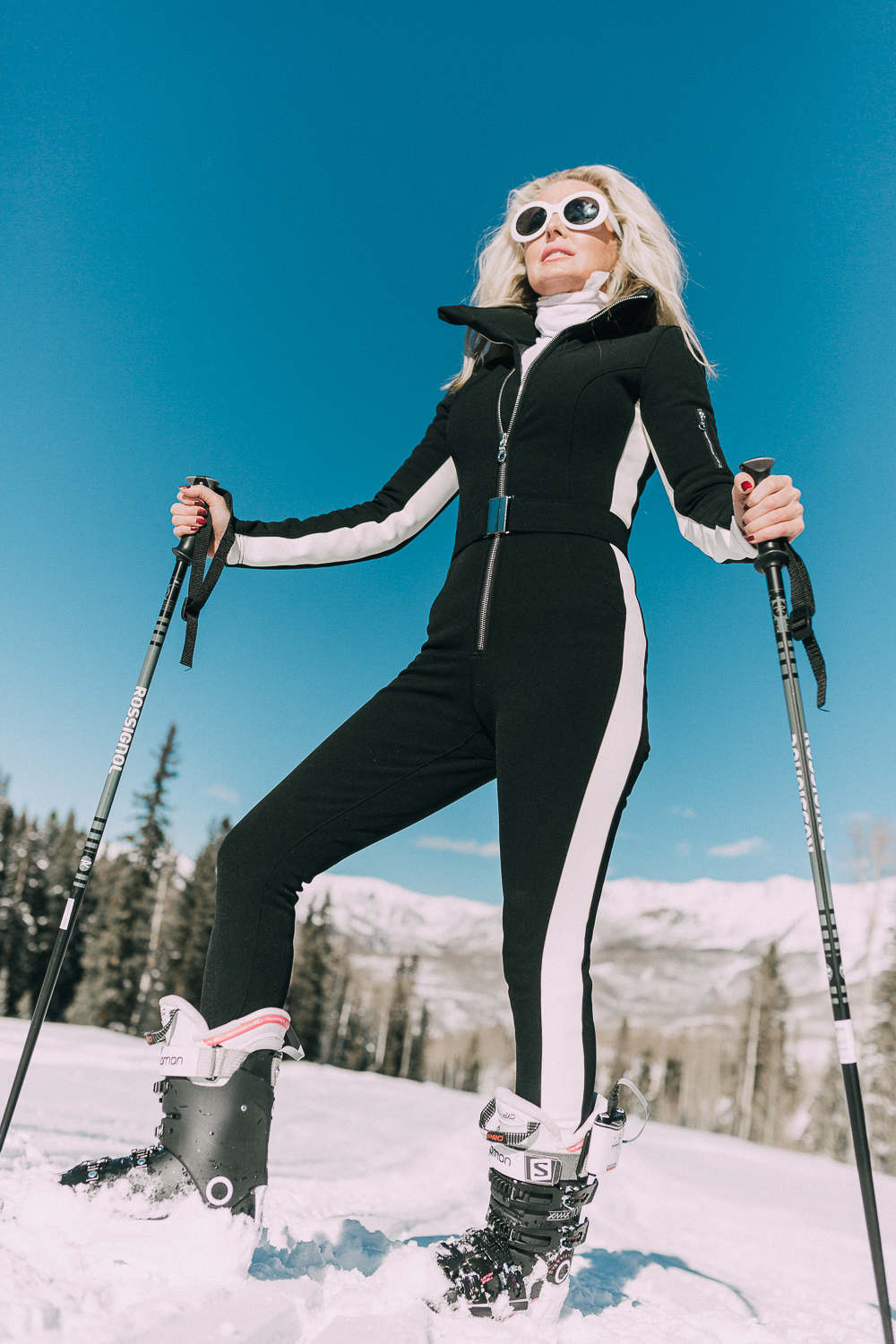 Ski Gear for women on eBay featuring a one-piece ski suit jumpsuit by Cordova on fashion blogger with blonde hair in snowy mountains, fashion blogger over 40 Erin Busbee of Busbeestyle.com