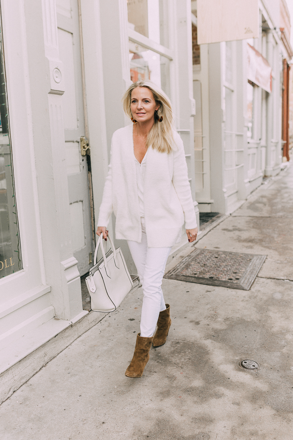 Fashion blogger Erin Busbee of BusbeeStyle.com wearing an all white look including a white fuzzy cardigan from Banana Republic, white faux wrap front blouse, and white jeans