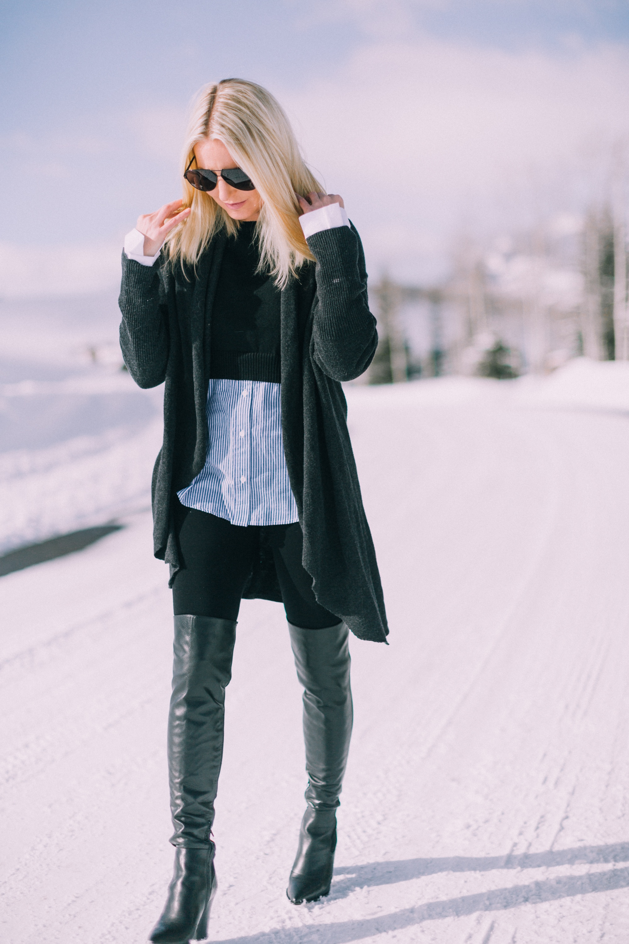 How to wear leggings over 40, featuring black Spanx leggings, Sam Edelman over the knee boots, Barefoot Dreams cardigan, and two-in-one layered sweater worn by fashion blogger Erin Busbee of busbeestyle.com in Telluride Colorado