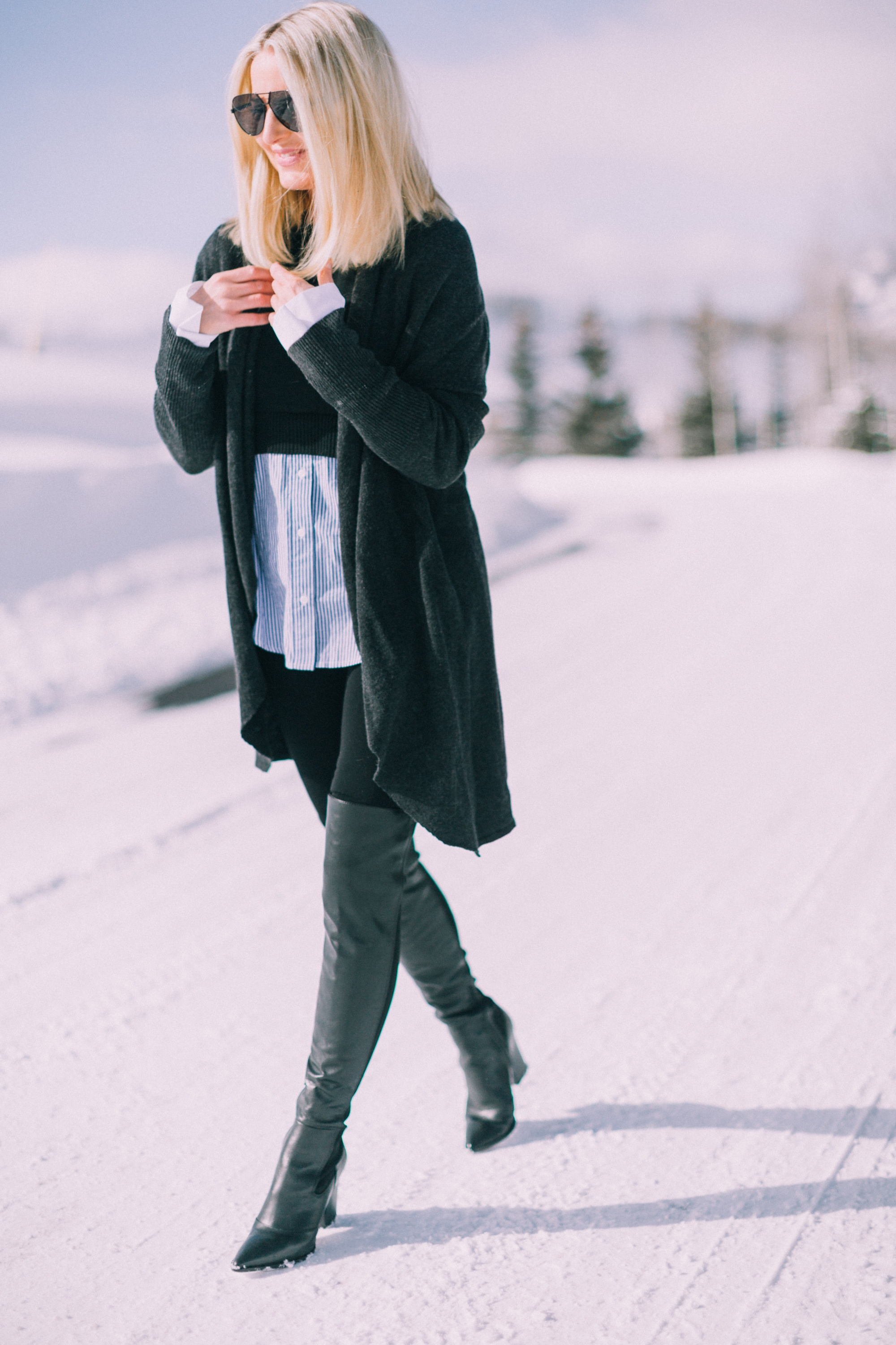 blond fashion blogger over 40 showing how to wear black Spanx leggings in an outfit with Sam Edelman Valda over the knee boots and Barefoot Dreams cardigan in the snow