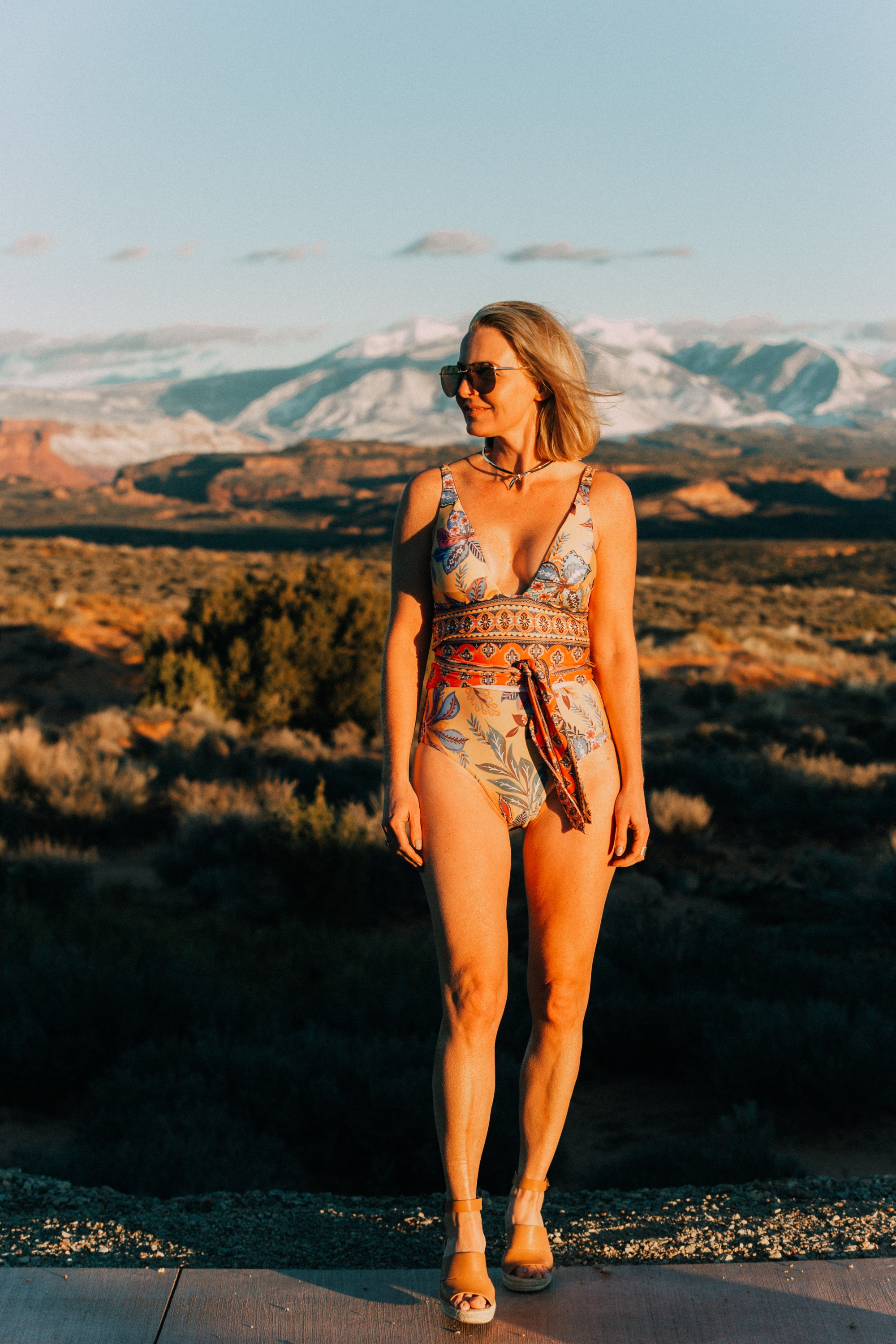 Full Coverage one piece paisley swimsuit by becca for women over 40 years old with Eddie Bargo choker necklace, and Treasure & Bond espadrille sandals in Moab, Utah