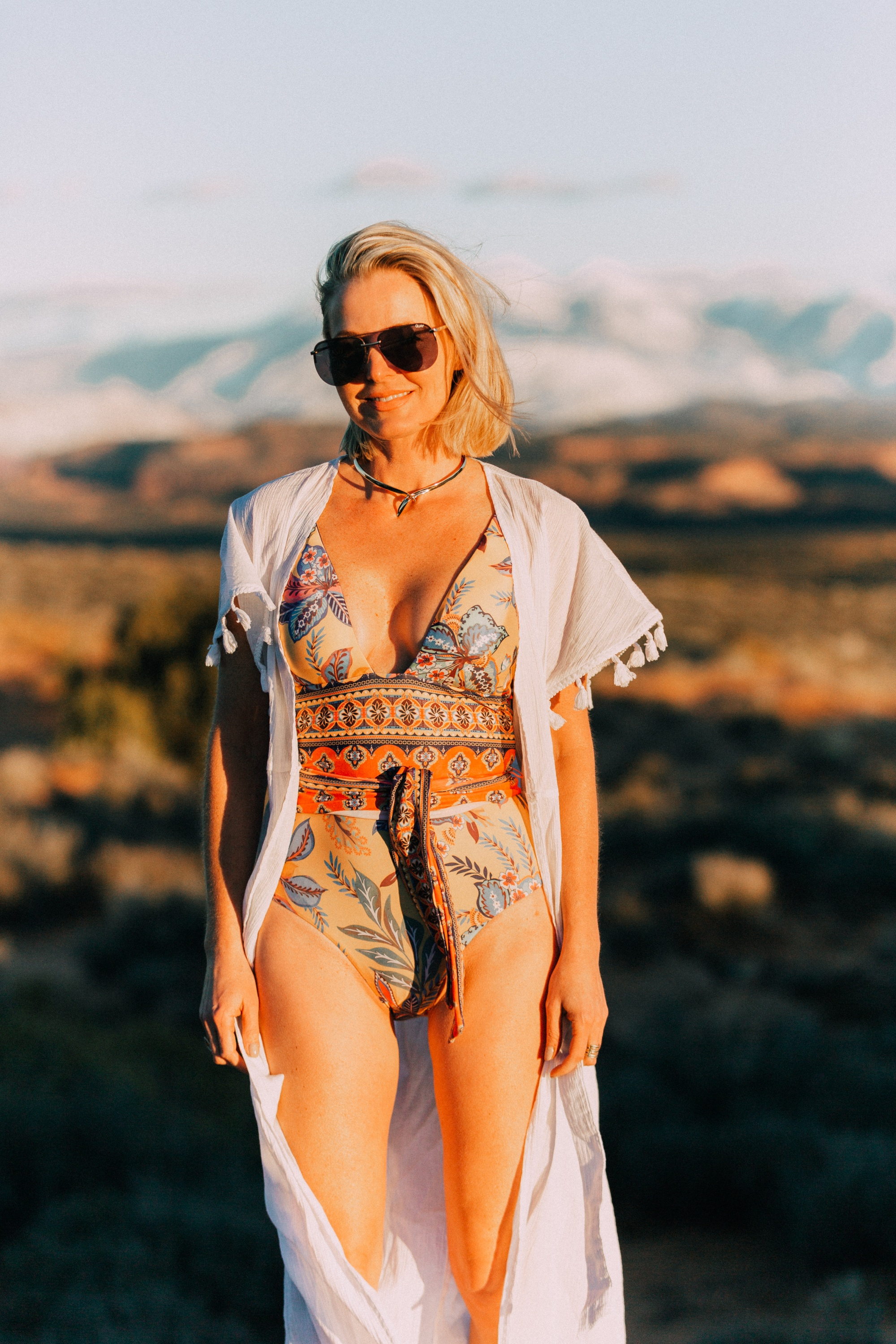 Full Coverage one piece paisley swimsuit by becca for women over 40 years old with Eddie Bargo choker necklace, and a white tassel kimono from Asos in Moab, Utah