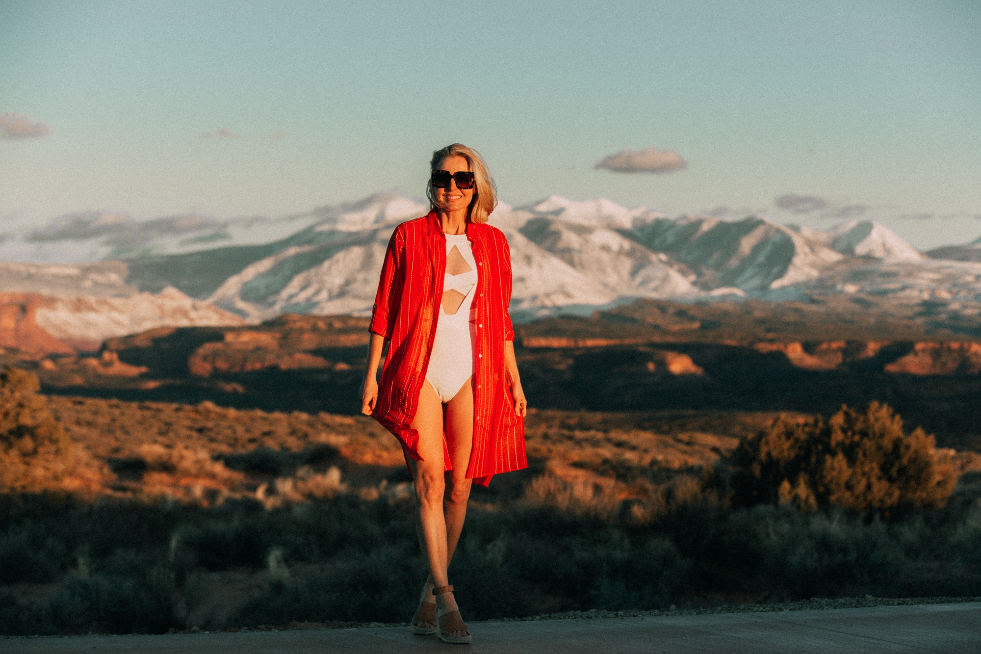 Full Coverage Swimsuits, fashion blogger Erin Busbee of BusbeeStyle.com wearing an orange Vix cover up with a white mesh OYE one piece swimsuit in Moab, Utah