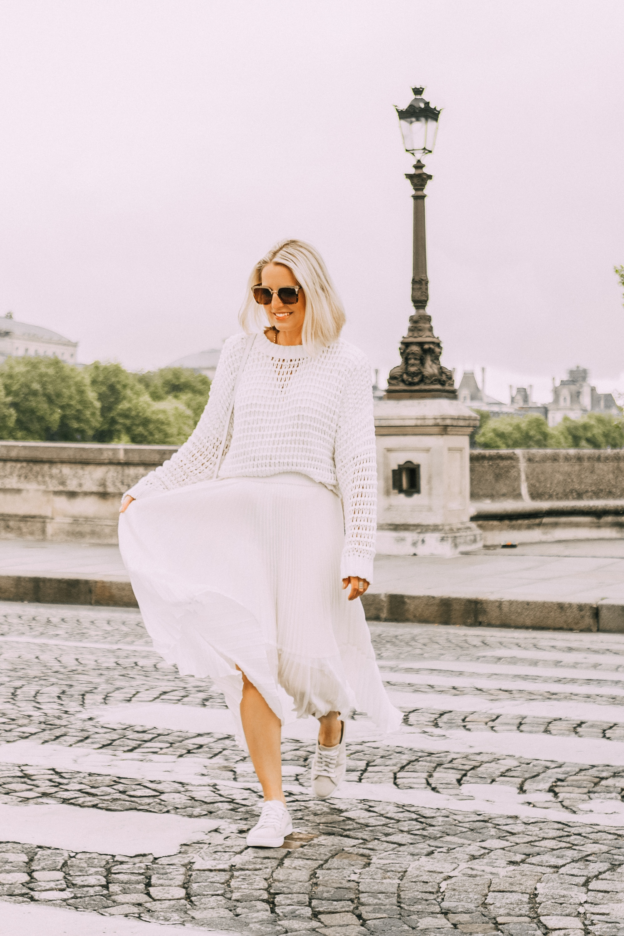 fashion blogger erin busbee walking in paris france wearing club monaco canvas sneaker mules white slouchy pullover knitted sweater ivory midi pleated skirt