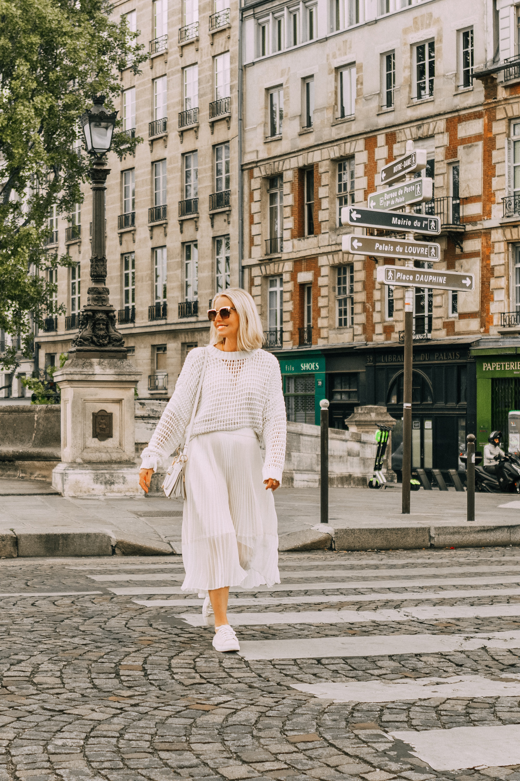 fashion blogger erin busbee walking in paris france wearing club monaco canvas sneaker mules white slouchy pullover knitted sweater ivory midi pleated skirt white givenchy calfskin whip bag