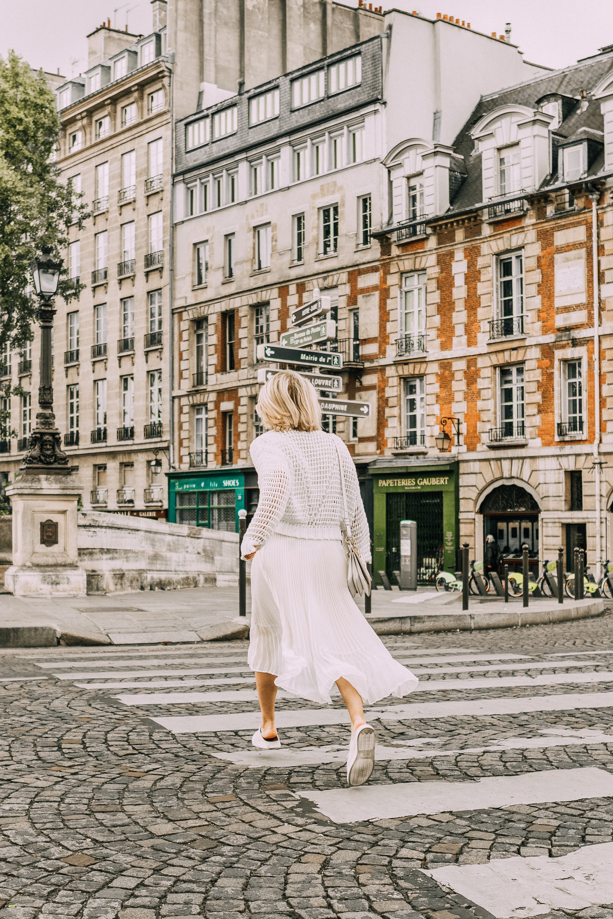 Best Travel Shoes, Fashion blogger Erin Busbee of BusbeeStyle.com wearing sneaker mules and pleated skirt by Club Monaco with a waffle knit sweater from Nordstrom in Paris, France