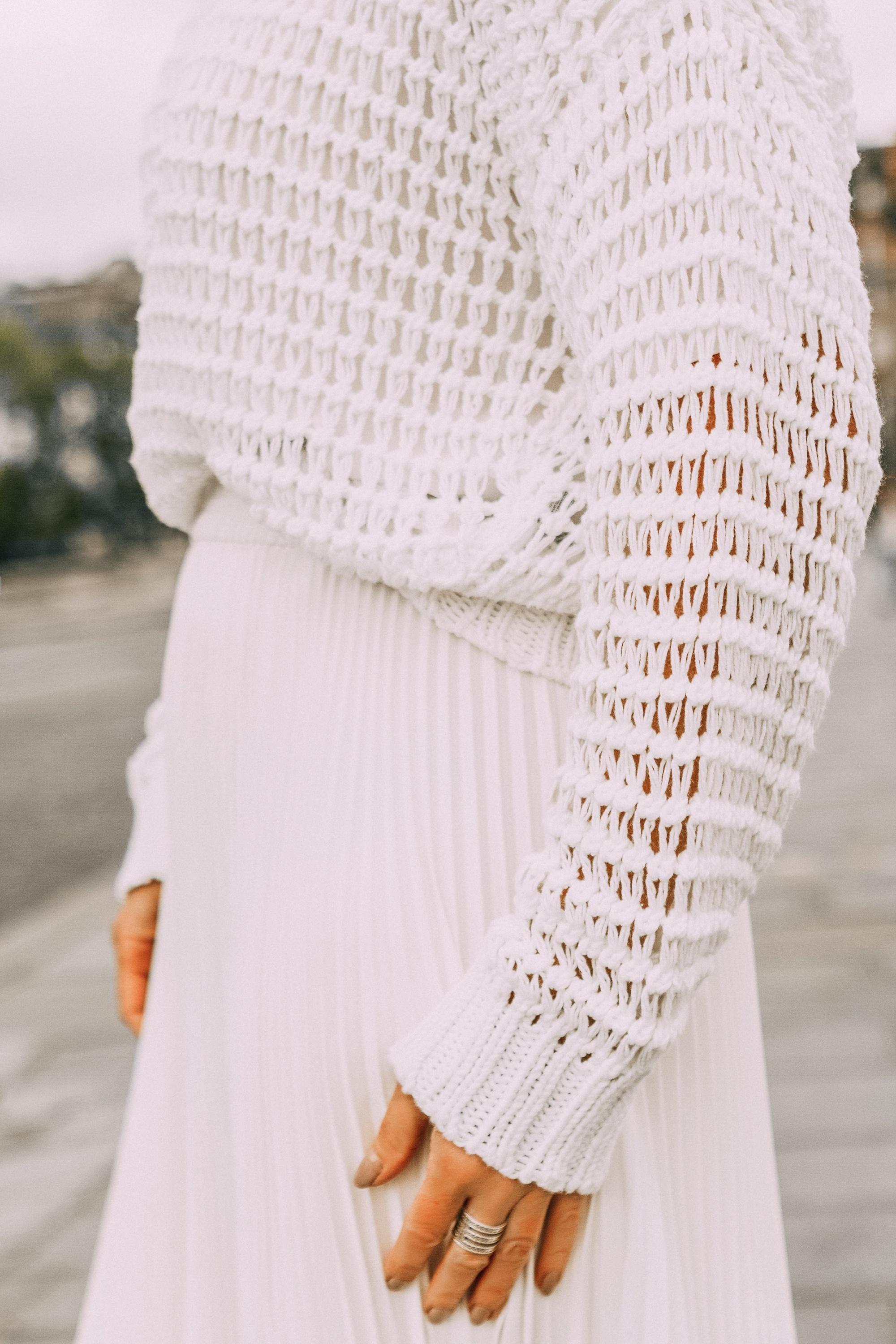 white slouchy pullover knitted sweater tucked into ivory midi pleated skirt