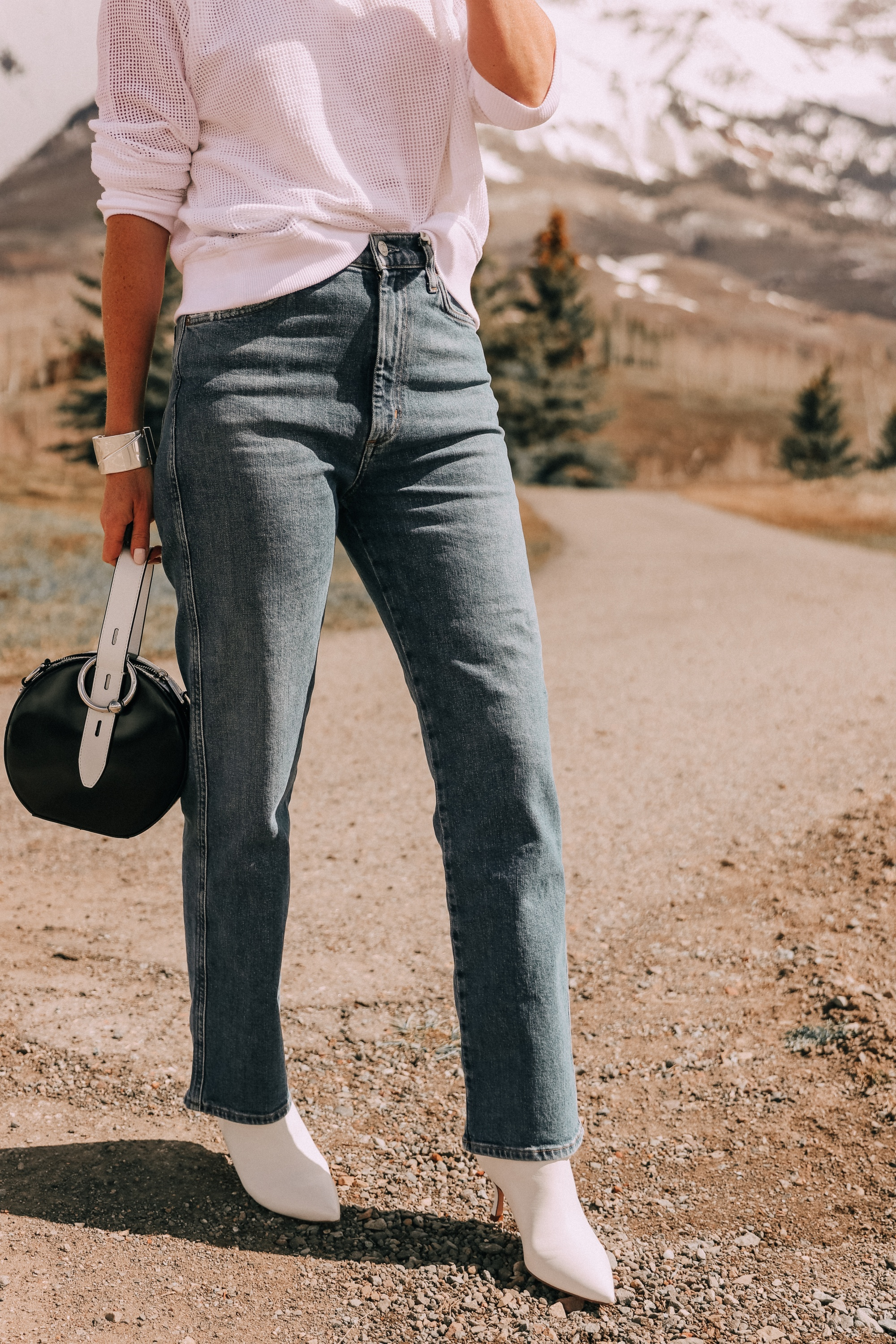 Lightweight Sweater For Summer, Fashion blogger Erin Busbee of BusbeeStyle.com wearing a white sweater by Eileen Fisher, with AGOLDE jeans, white Stuart Weitzman booties, and a black and white Rebecca Minkoff bag from Bloomingdale's in Telluride, CO