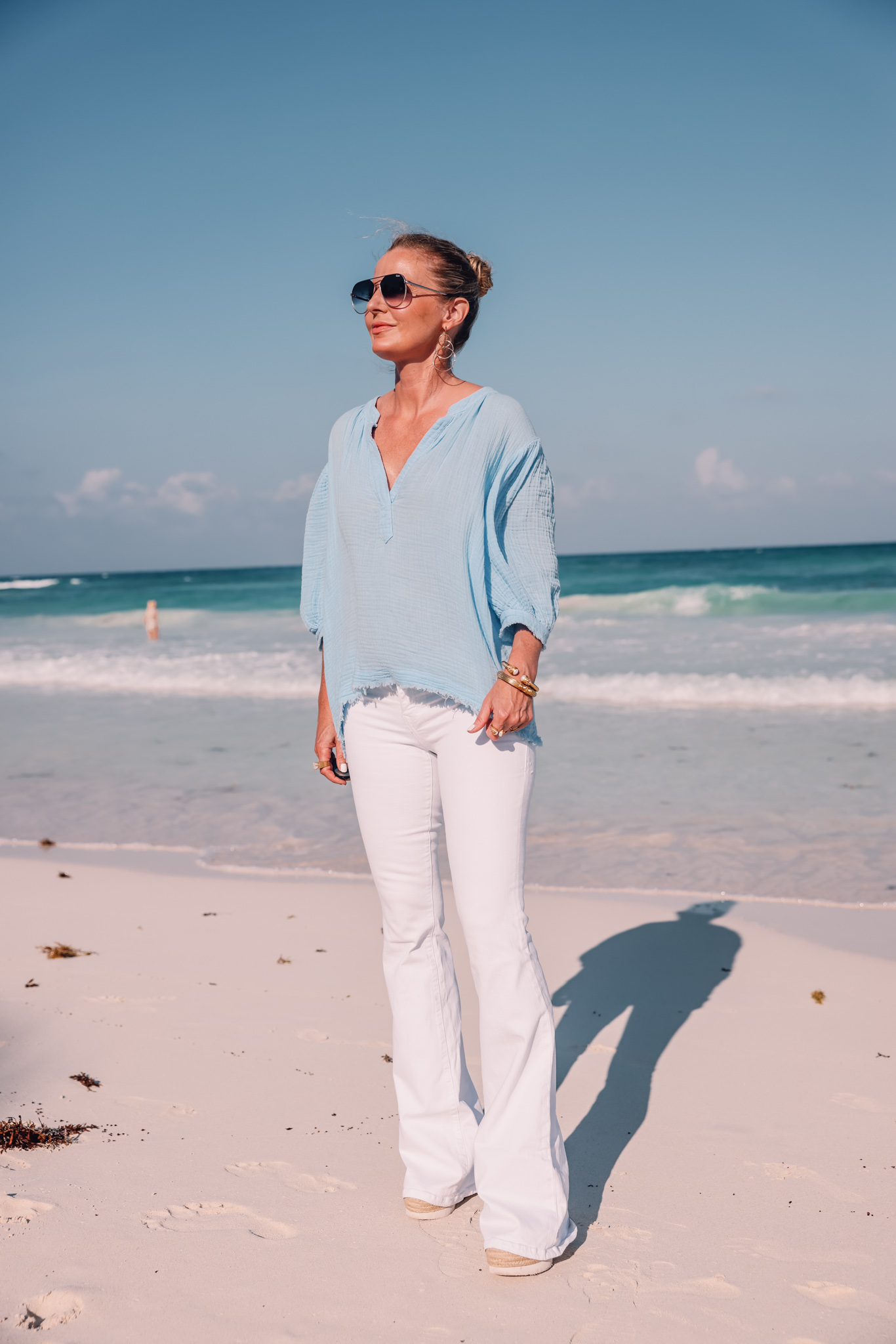 blue cotton gauze 9seed top paired with white jeans on fashion over 40 blogger Erin Busbee at beach