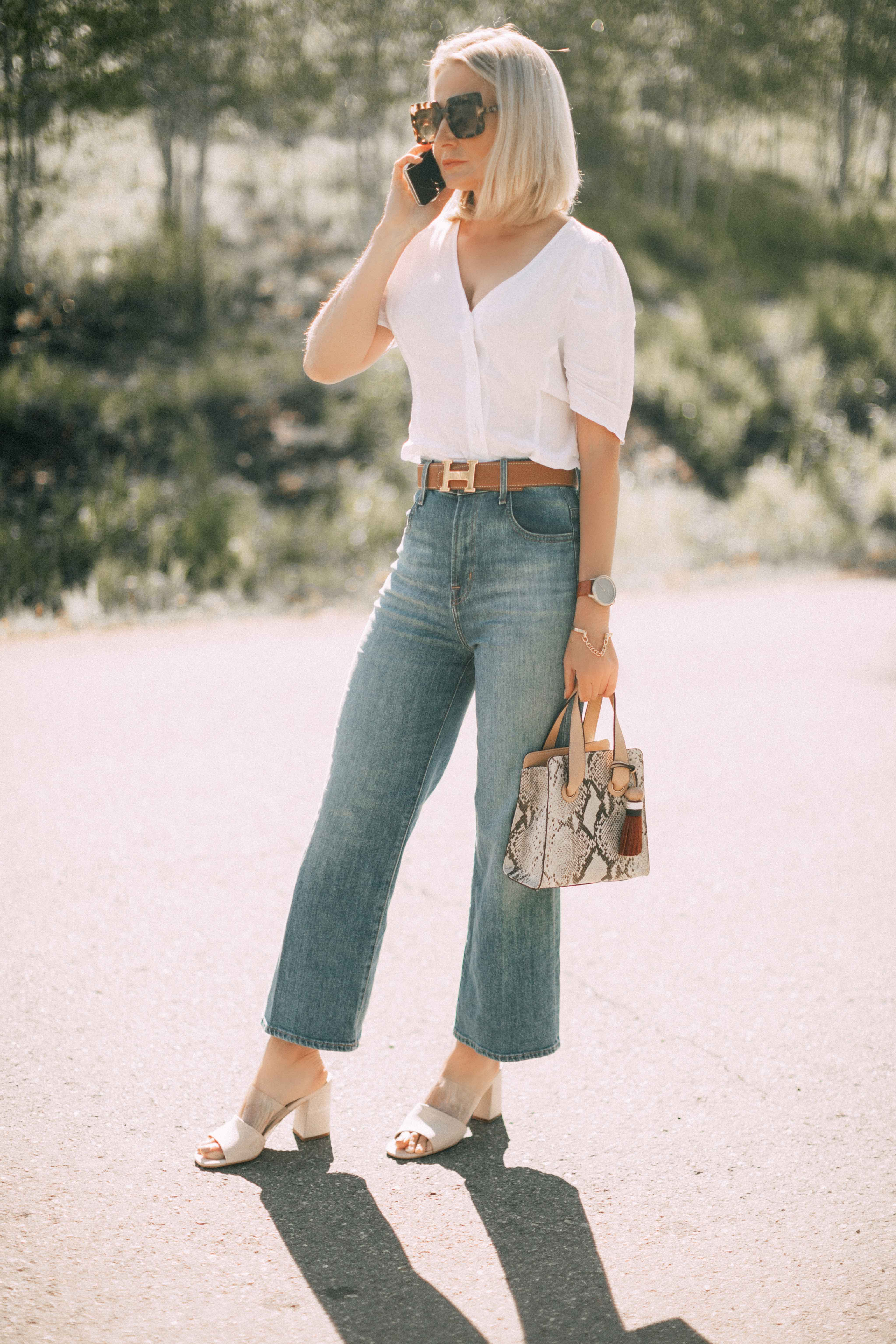 Lucite Trend, Fashion blogger Erin Busbee of BusbeeStyle.com wearing lucite mules from Vince Camuto with J Brand jeans, white Leith top, Hermes belt, and a python print Vince Camuto bag in Telluride, Colorado