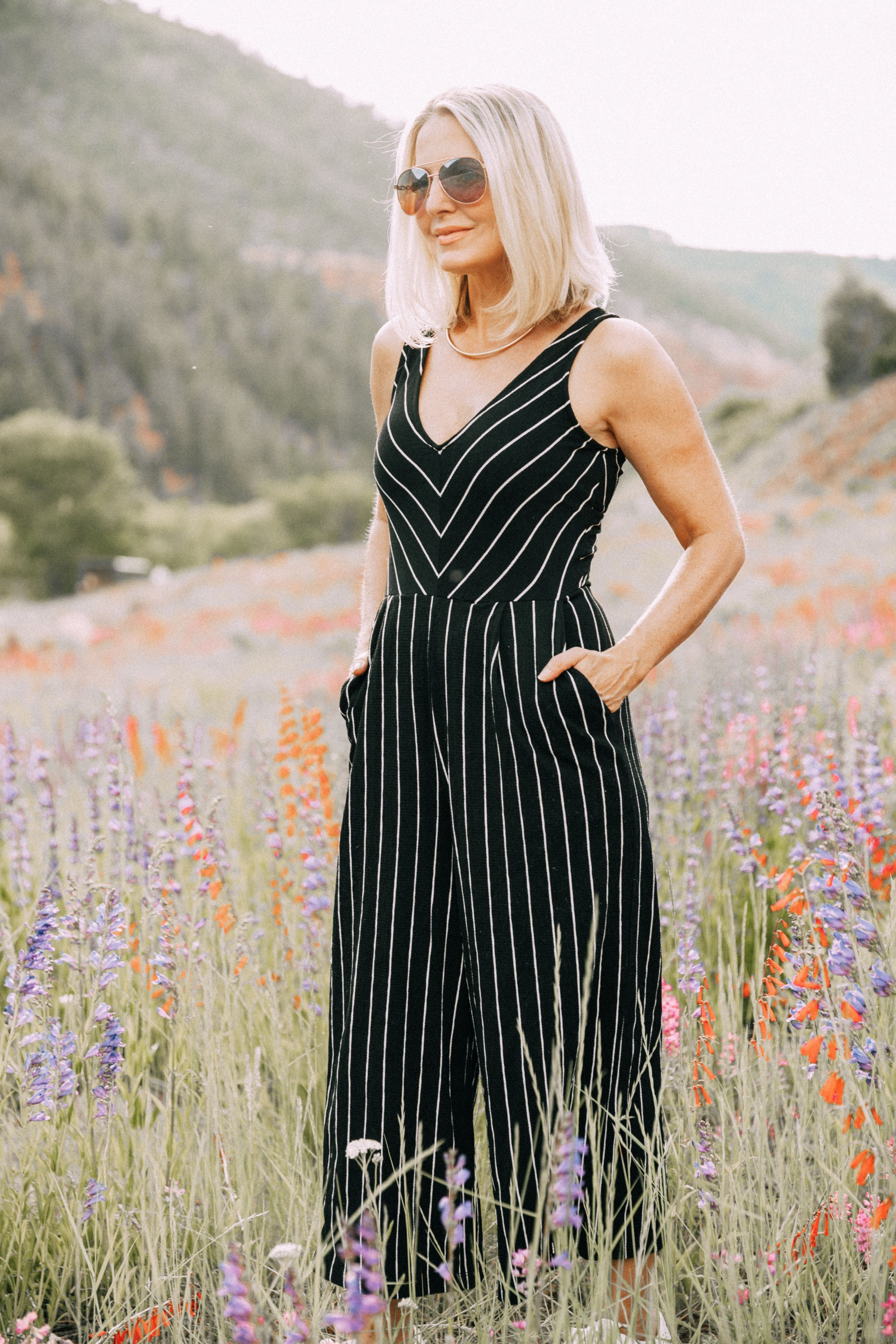 Ways To Wear Stripes, Fashion blogger Erin Busbee wearing a striped black and white jumpsuit and white perforated sneakers from JCPenney in the wildflowers in Telluride, CO