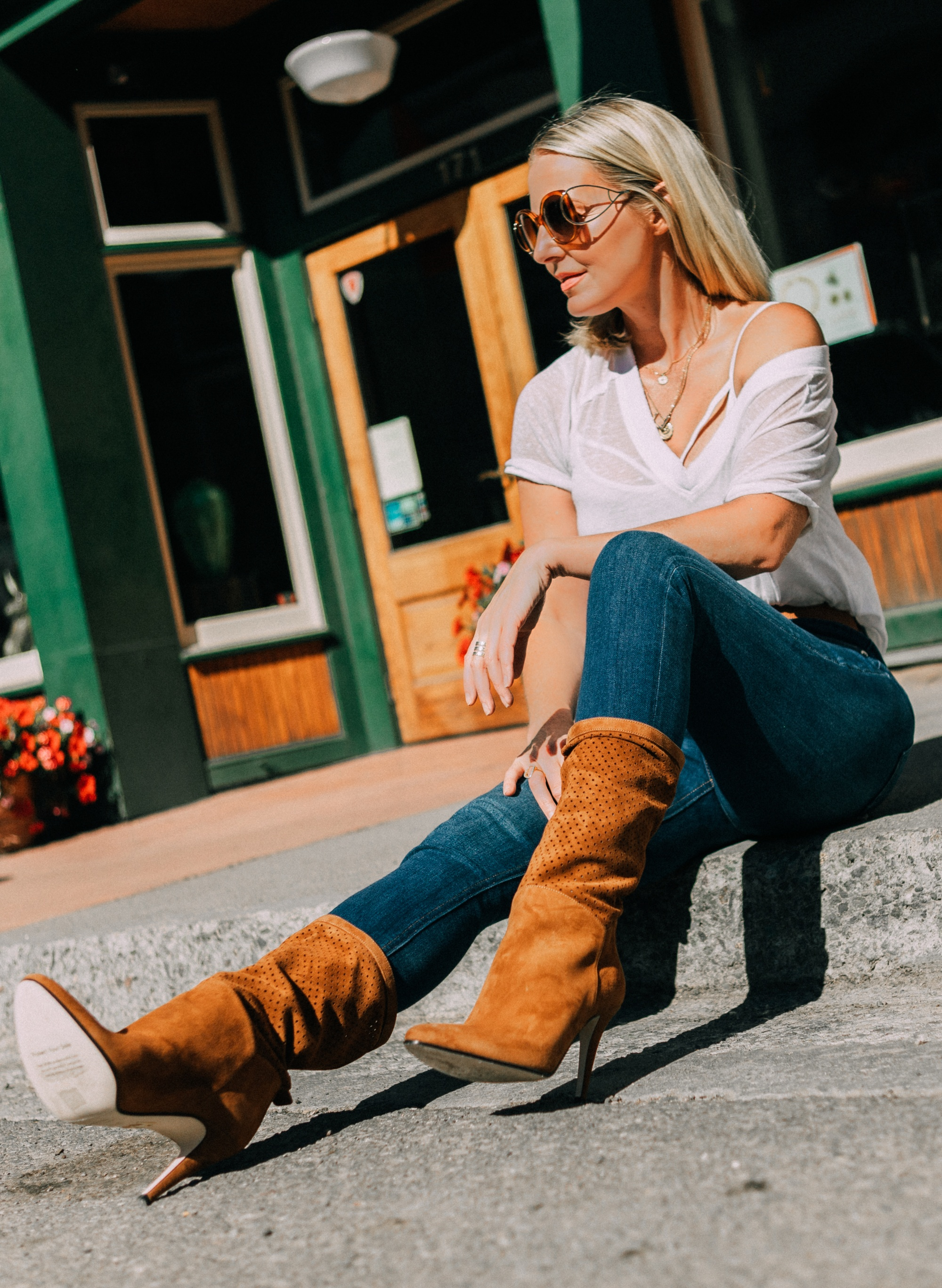 Tamara Mellon, Fashion blogger Erin Busbee of BusbeeStyle.com wearing dark was skinny jeans and white tee with stunning Tamara Mellon perforated brown boots in Telluride, Colorado