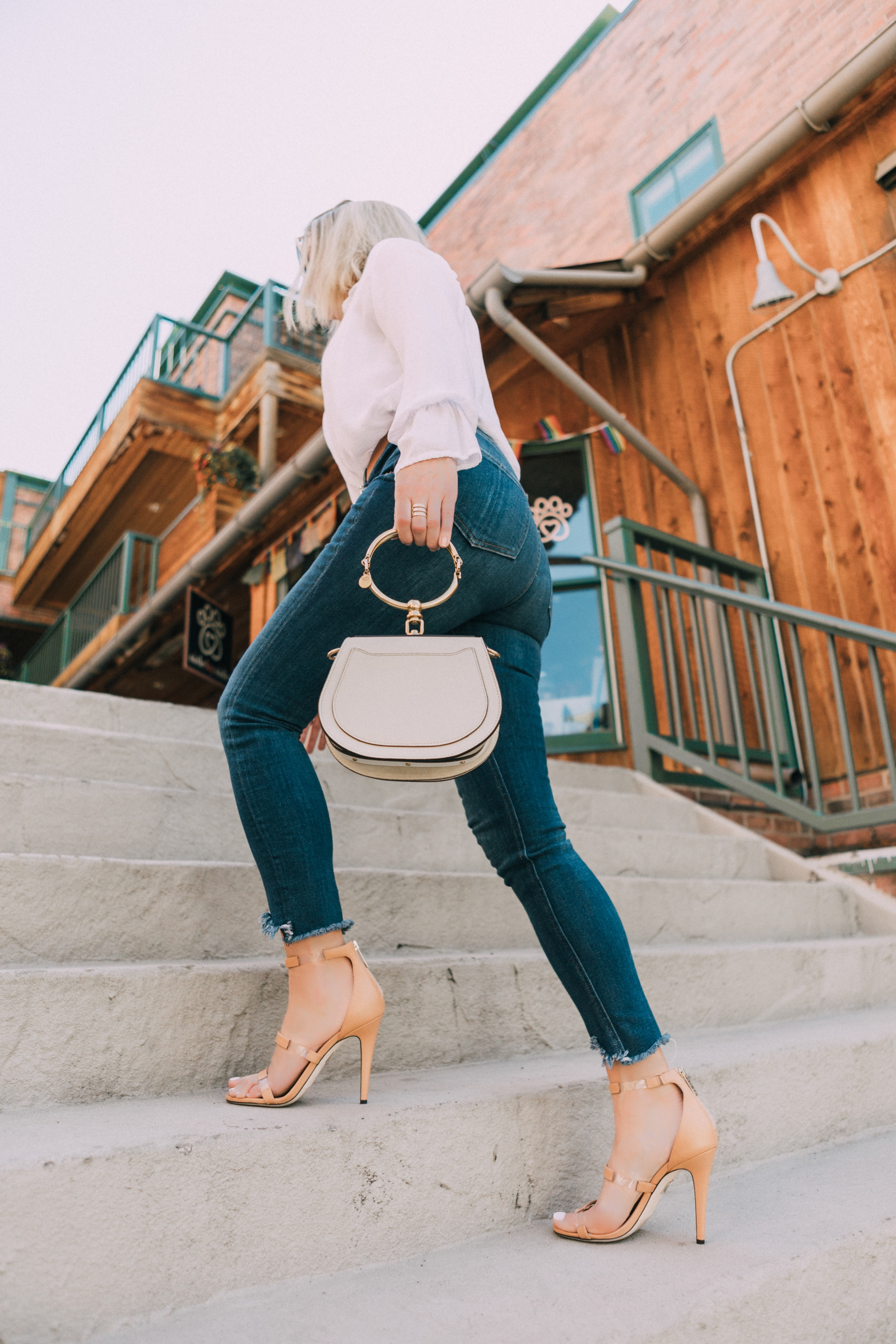 Tamara Mellon, Fashion blogger Erin Busbee of BusbeeStyle.com wearing dark was skinny jeans and white top with stunning Tamara Mellon Frontline heels in Telluride, Colorado