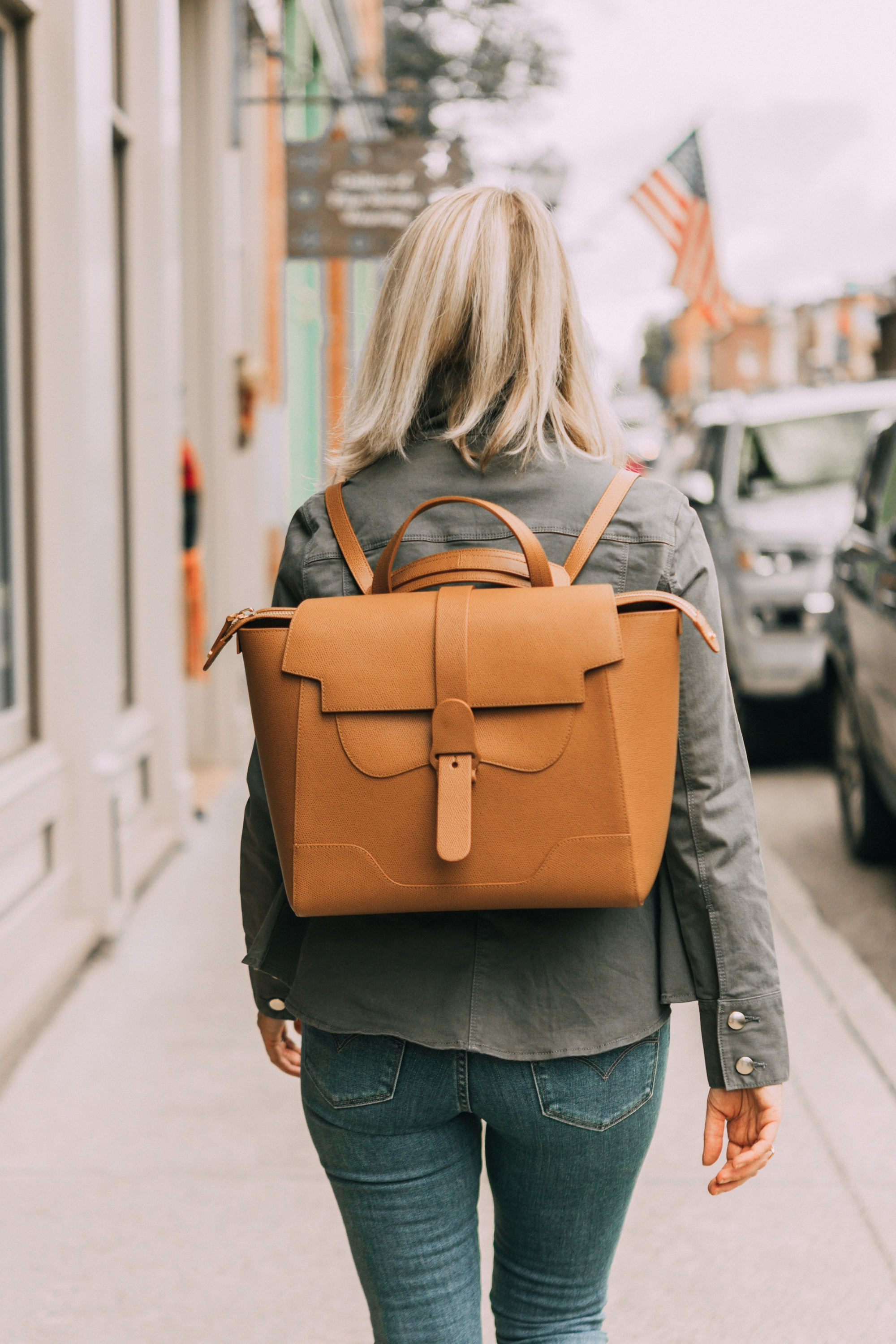 Hot Handbags, Fashion blogger Erin Busbee of BusbeeStyle.com wearing the brown Senreve Maestra Bag with Levi jeans, white cami, and Frame peplum hem green jacket in Telluride, Colorado