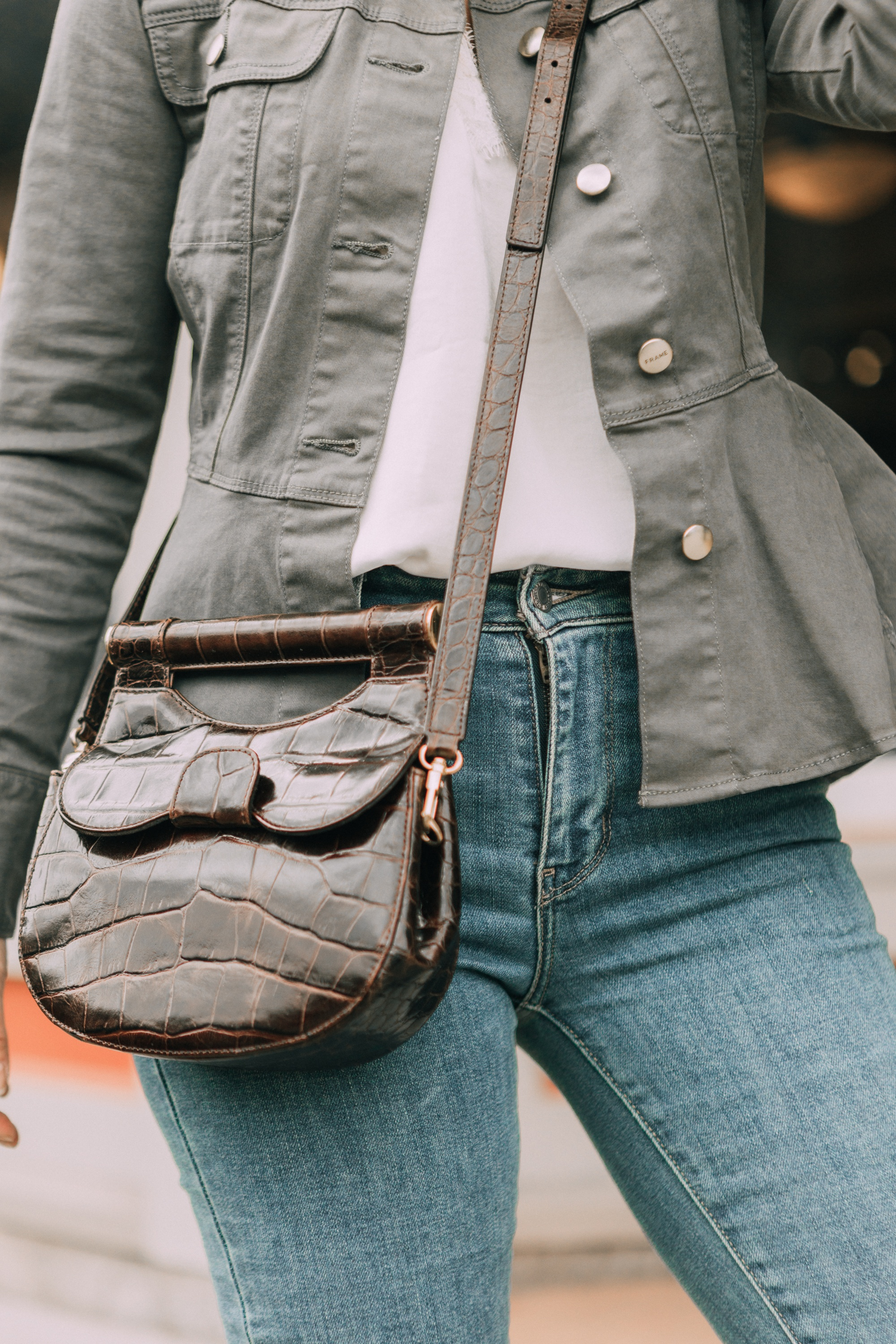 Hot Handbags, Fashion blogger Erin Busbee of BusbeeStyle.com wearing the brown STAUD Madeline Croc-Embossed Crossbody Bag with Levi jeans, white cami, and Frame peplum hem green jacket in Telluride, Colorado