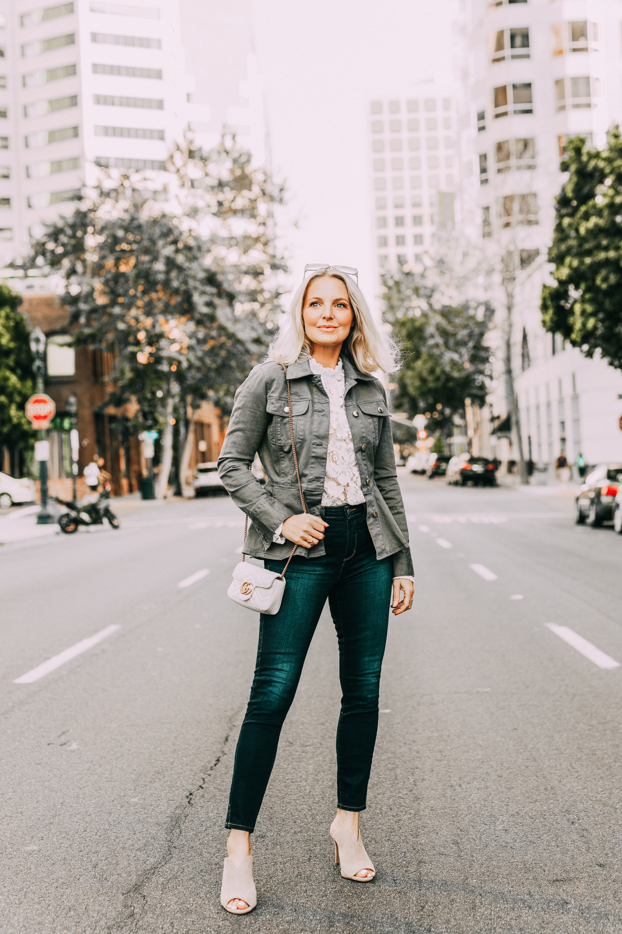 White Top Under $100, Fashion blogger Erin Busbee of BusbeeStyle.com wearing a white lace top by WAYF with dark wash skinny jeans by L'AGENCE, neutral Vince Camuto peep-toe mules, a white mini Gucci bag, and green peplum Frame jacket in San Diego, California