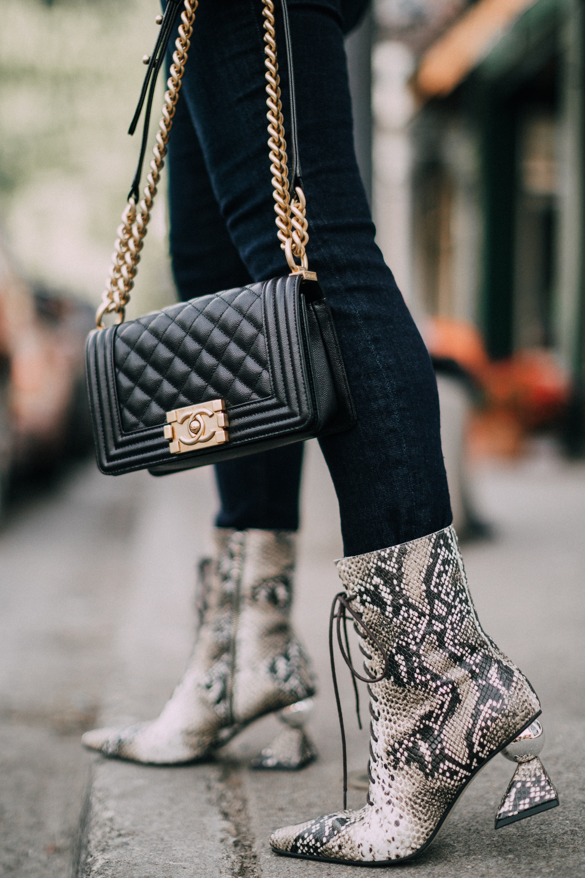 Yuul Yie, Fashion blogger Erin Busbee of BusbeeStyle.com wearing dark wash skinny jeans by L'Agence, leopard print bodysuit by ASTR the label, black Chanel boy bag, and Yuul Yie python boots in Telluride, CO