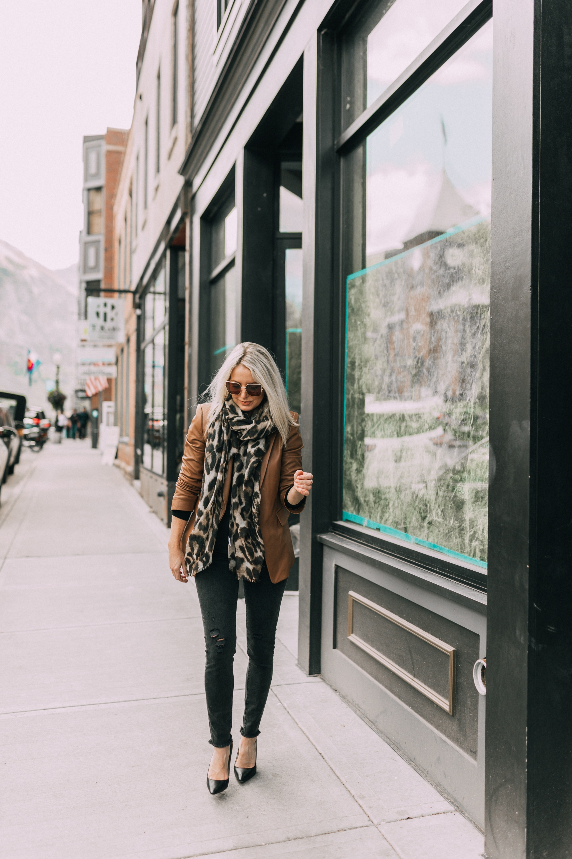 Brown and black outfit, fashion blogger Erin Busbee of BusbeeStyle.com wearing a brown leather blazer by Kobi Halperin, black distressed jeans by J Brand, black puff sleeve cashmere sweater by AQUA, gold Baublebar layered necklace, leopard print scarf, and black Jimmy Choo pumps in Telluride, Colorado