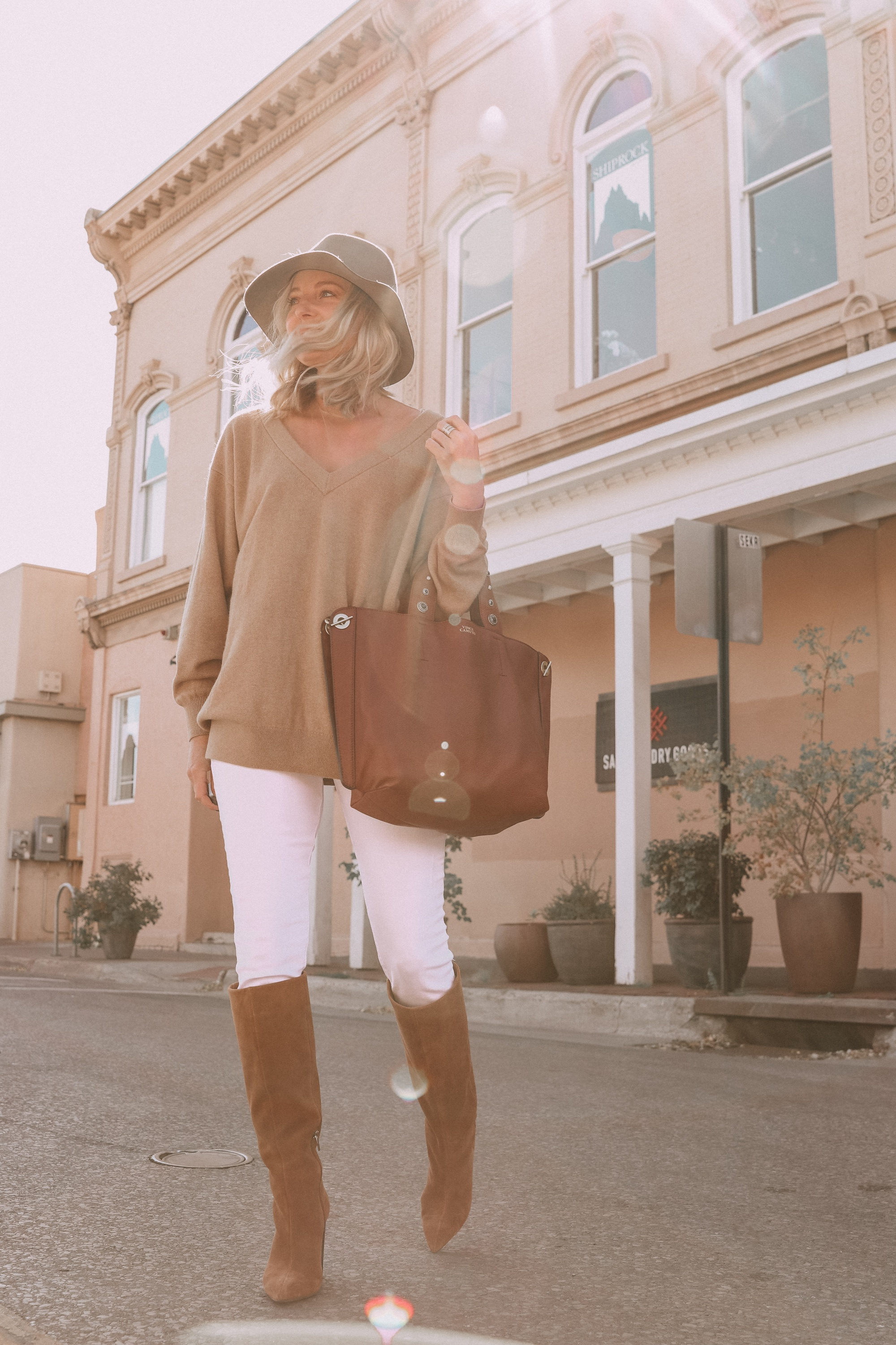 Brown Accessories For Fall, Fashion blogger Erin Busbee of BusbeeStyle.com wearing brown boots and brown tote from Vince Camuto with white jeans, camel sweater, leopard scarf, and Rag & bone hat in Santa Fe, New Mexico
