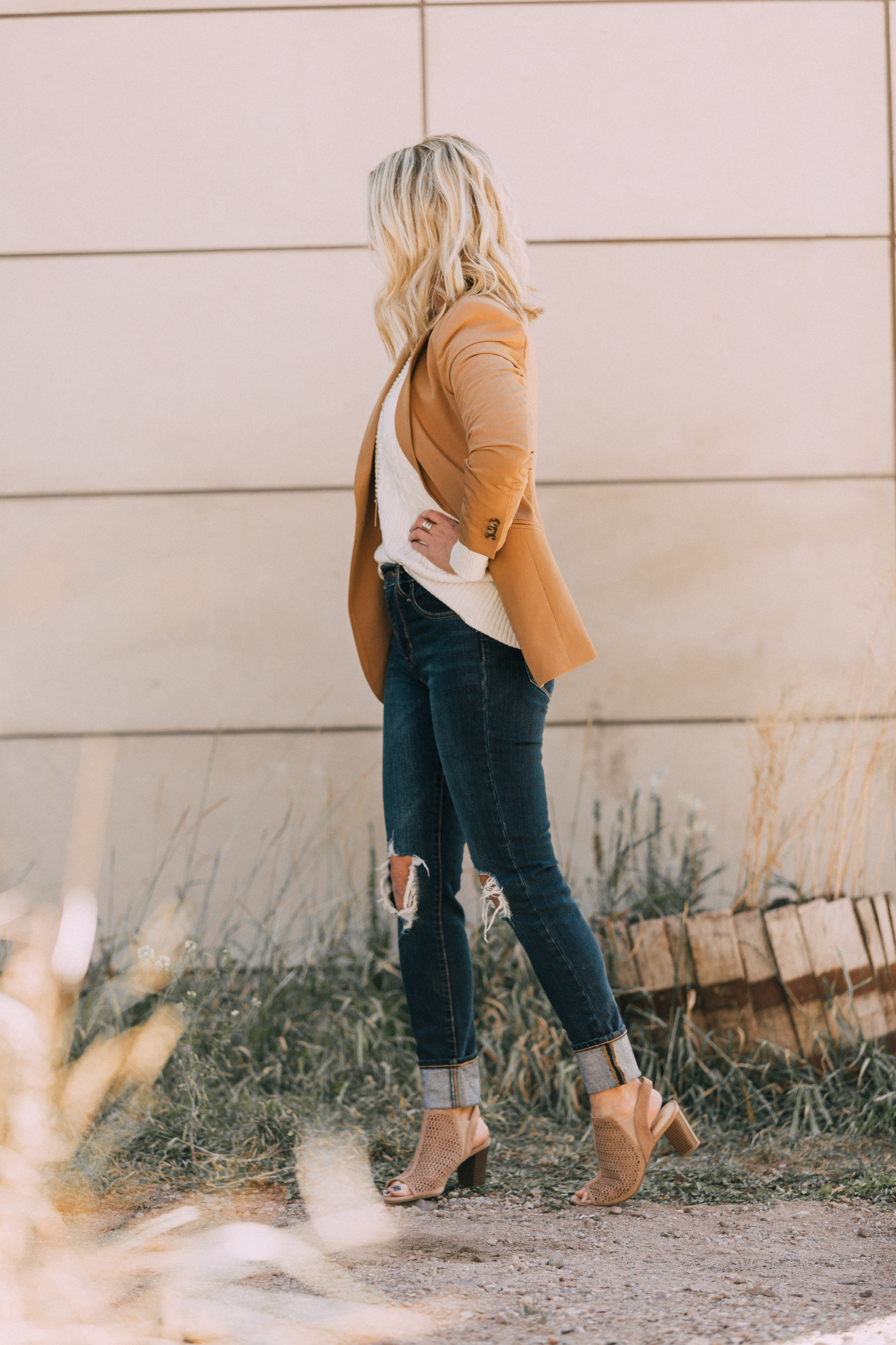 affordable camel colored blazer with blue jeans and white cable knit sweater open toe perforated nude booties