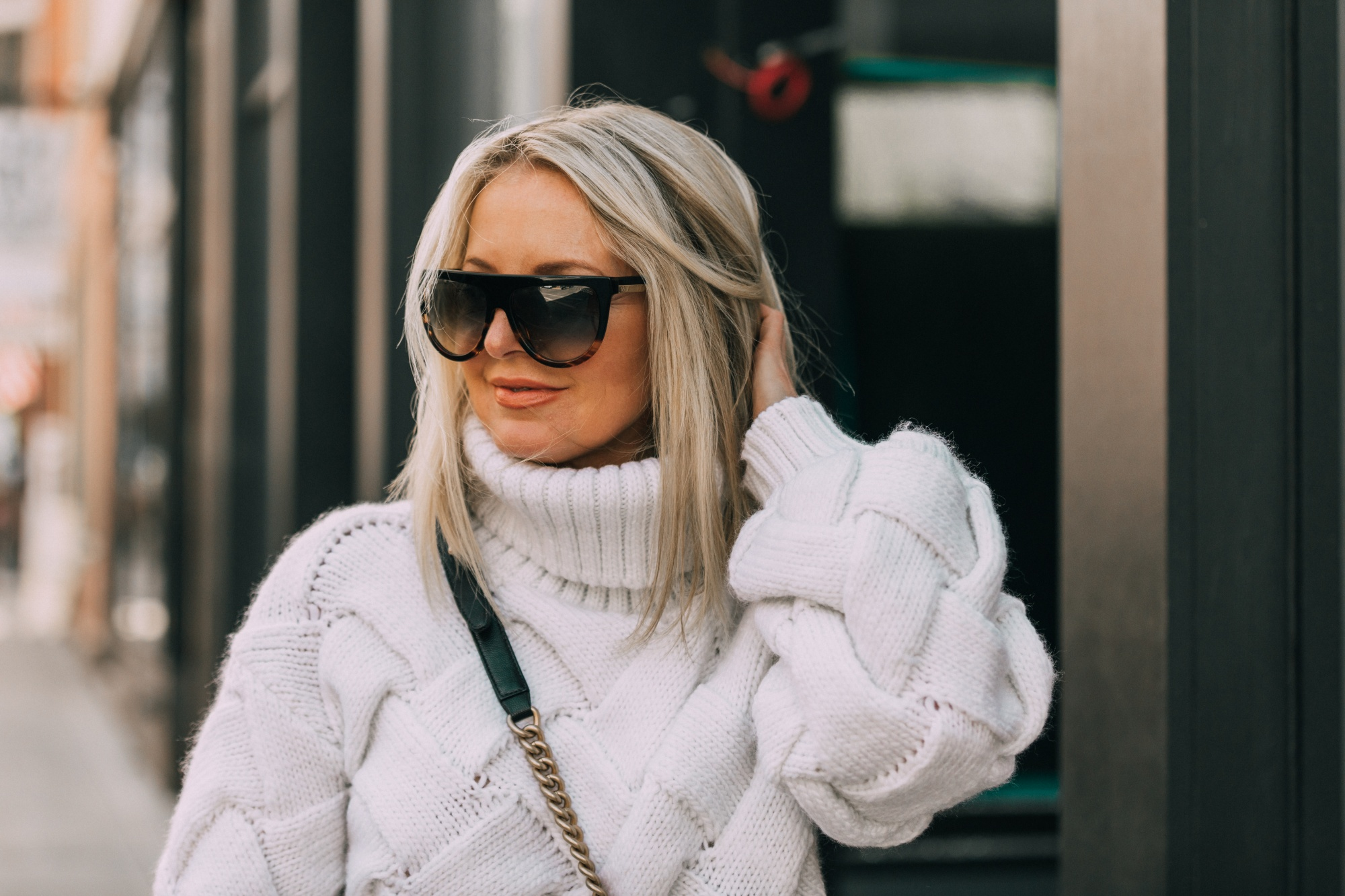 fashion blogger showing how to style dad sneakers in outfit with white chunky sweater for fall chanel handbag