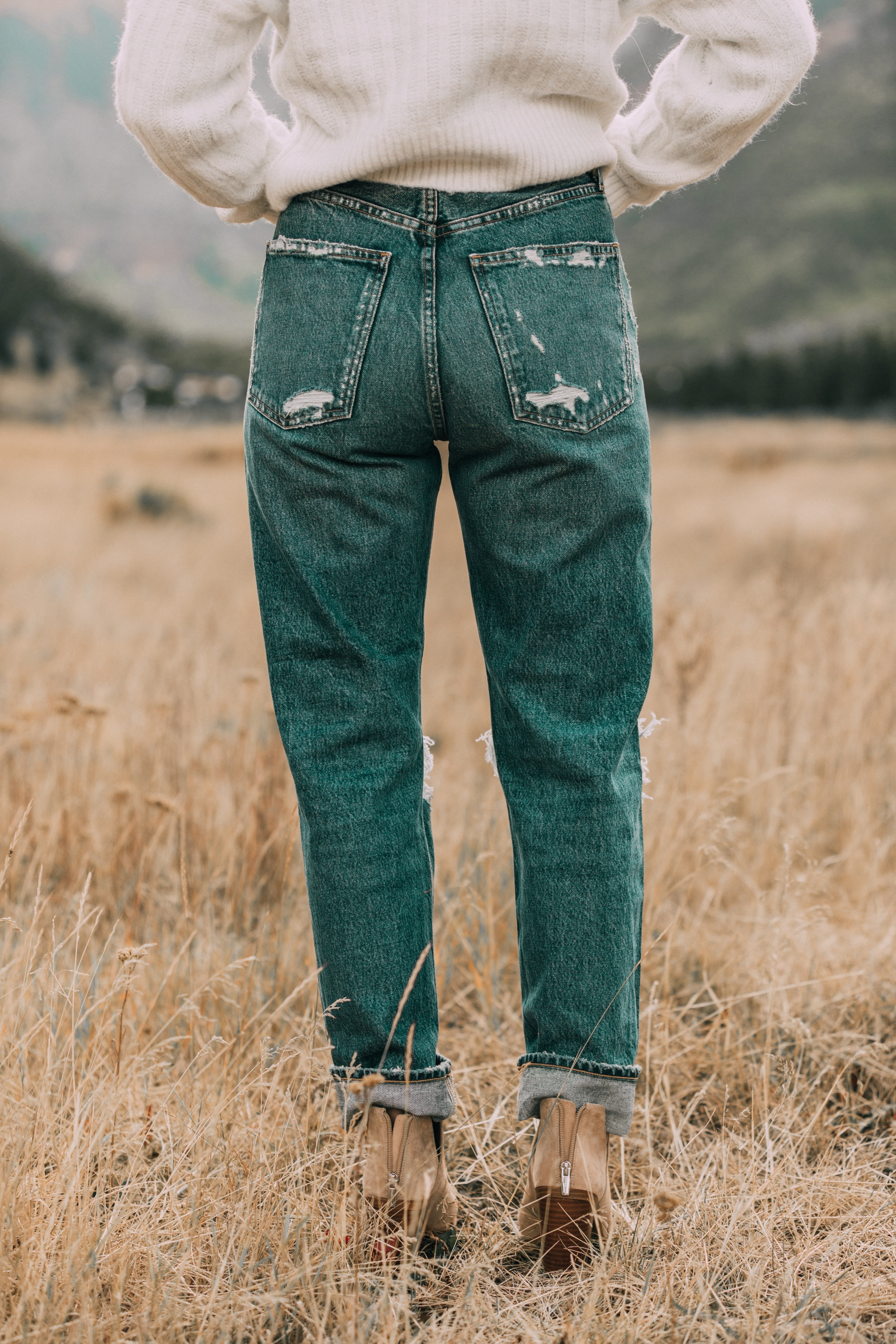 Baggy Jeans trend, Fashion blogger Busbee Style wearing Agolde baggy oversized jeans with Sam Edelman booties, white Express cable knit sweater in Telluride, CO