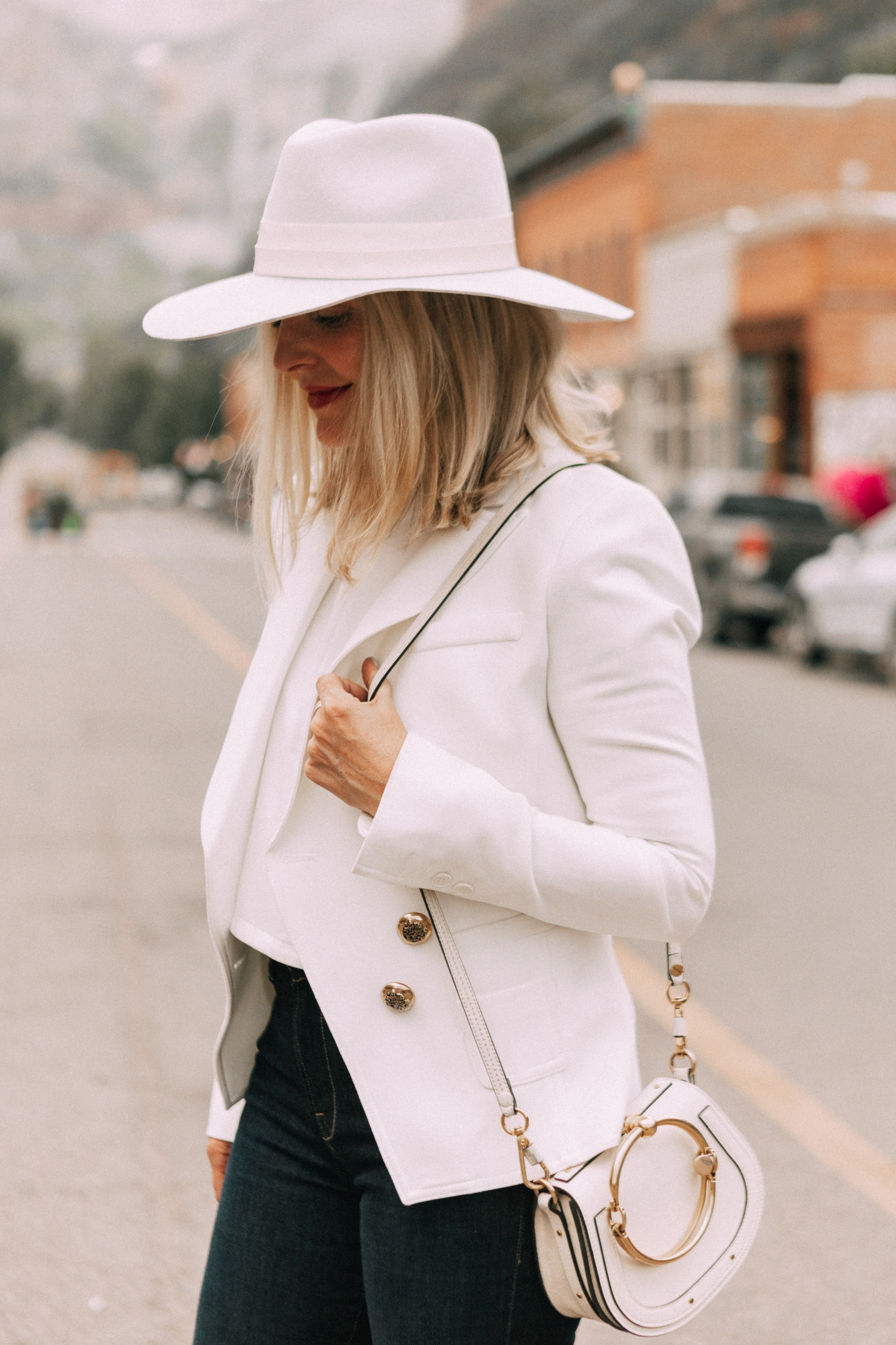 erin busbee wearing a white wool fedora hat with leather hat band fedora white blazer over white top paired with dark skinny jeans