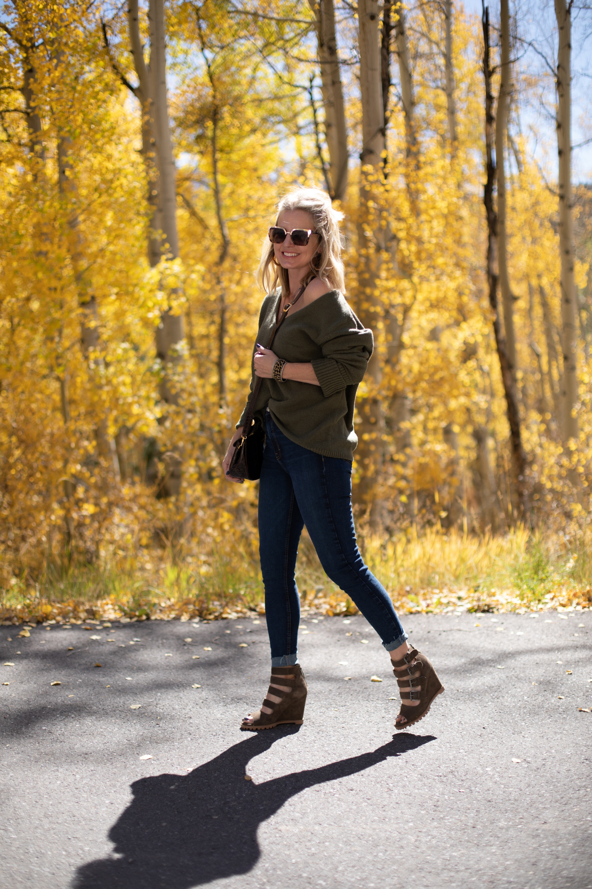 Shoes For Busy Women, Fashion blogger Erin Busbee of BusbeeStyle.com wearing Linea Paolo Wisteria Buckle Wedge Sandals with rag & bone skinny jeans, Something Navy green sweater, Staud Madeline Croc Embossed crossbody, and Quay sunglasses in Telluride, CO