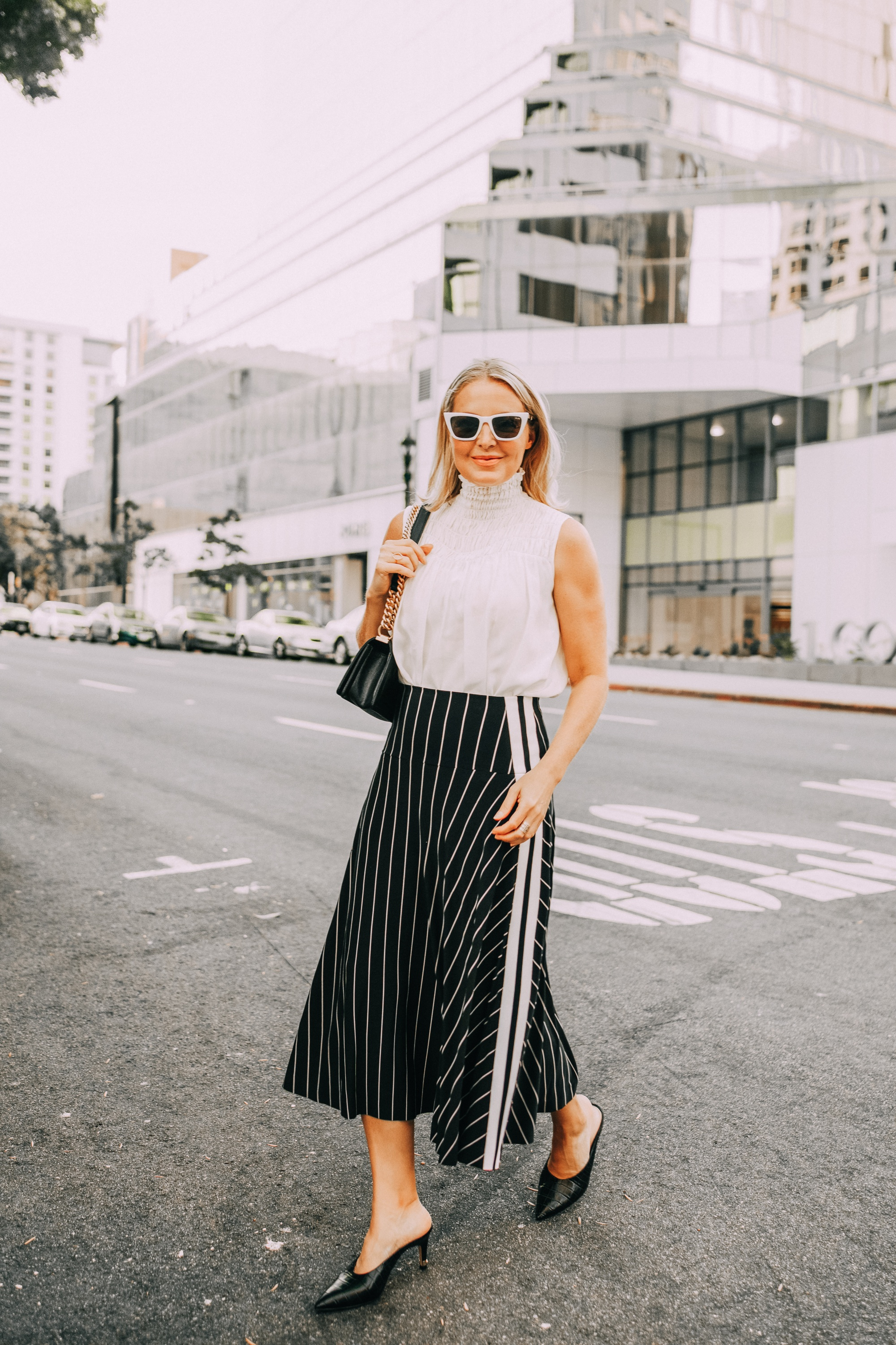 smocked high neckline white sleeveless blouse outfit with black and white stripe skirt