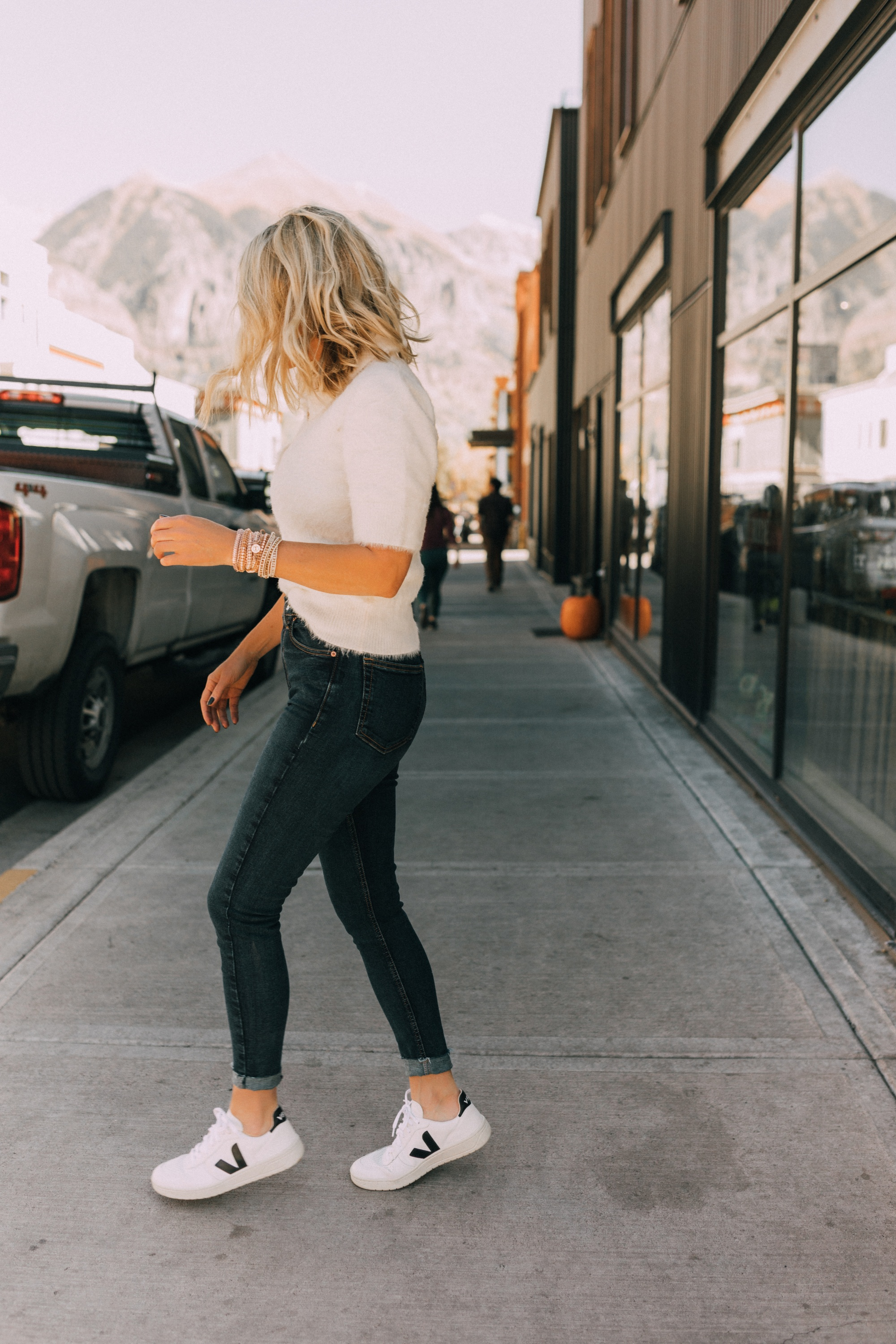 Fall Jewelry, Fashion blogger Erin Busbee of BusbeeStyle.com wearing three wrap bracelets by Victoria Emerson with dark wash skinny jeans, white fuzzy polo sweater, and Veja sneakers in Telluride, CO