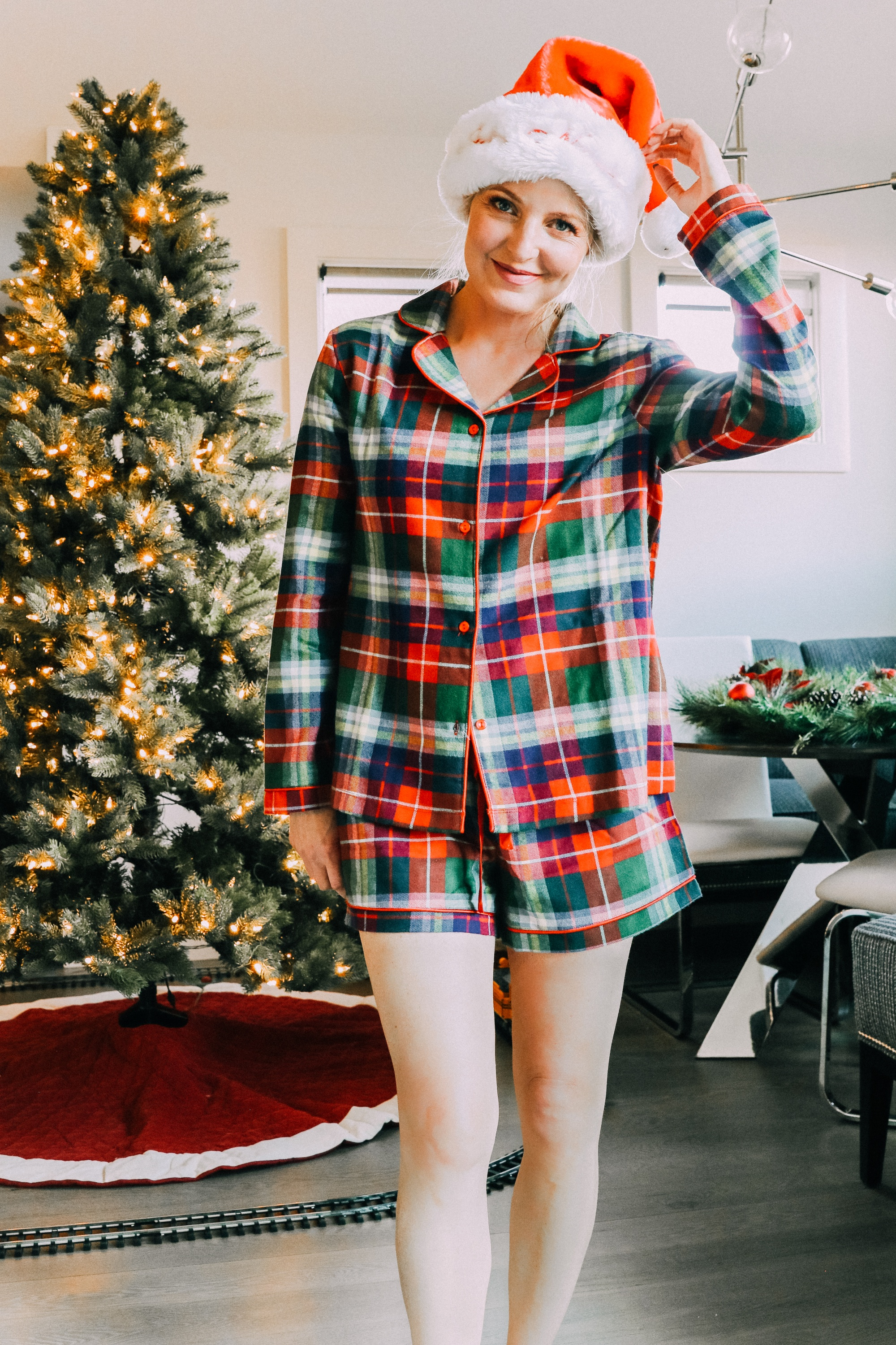 How to make holiday decorating easier, Fashion blogger Erin Busbee of BusbeeStyle.com sharing how to make the holidays more stress free wearing plaid pajamas shorts and top by Jockey and a Santa hat by her pre-lit tree in Telluride, CO