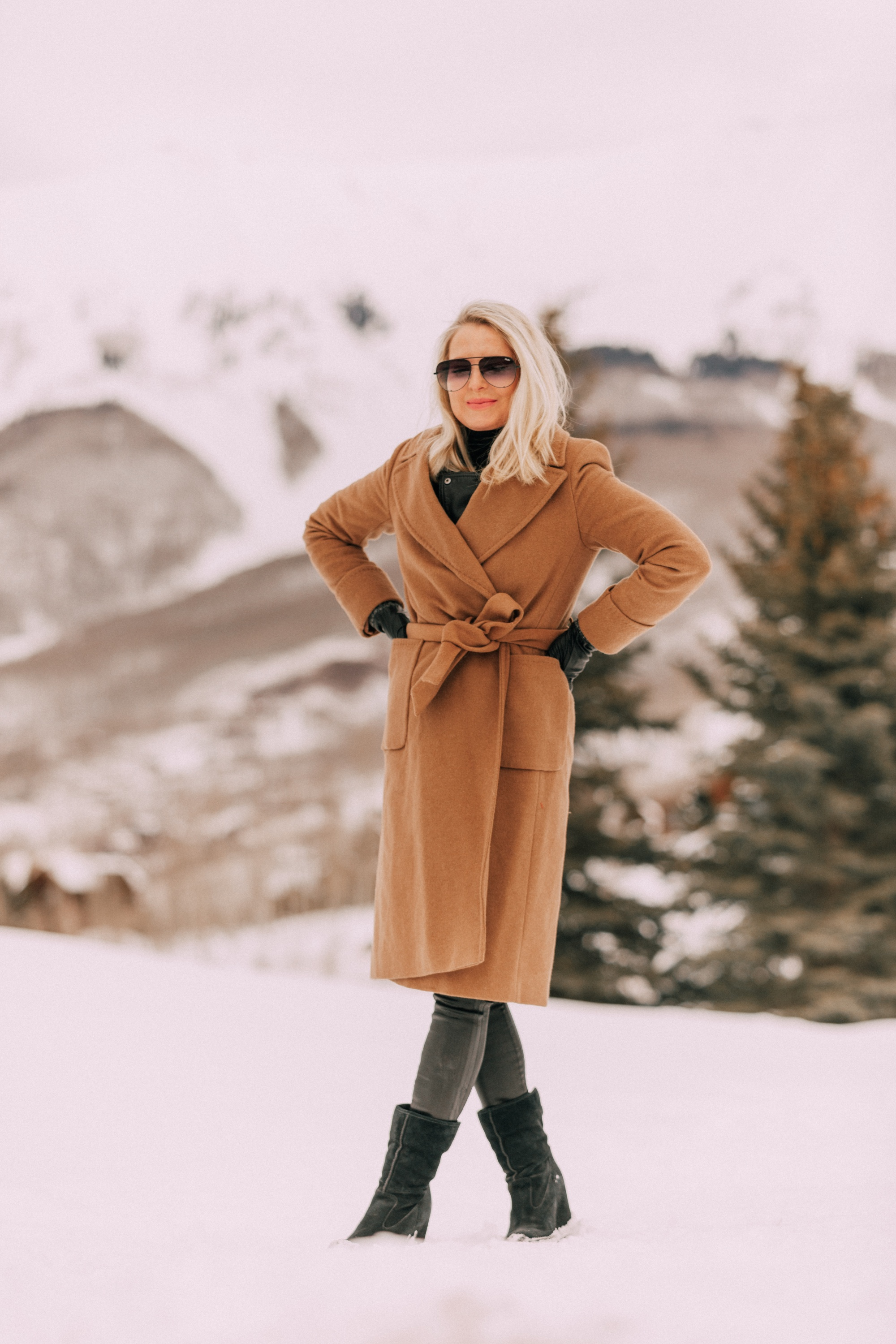How To Layer A Moto Jacket, Fashion blogger Erin Busbee of BusbeeStyle.com wearing a black leather IRO moto jacket, Carolina Amato gloves, rocket leatherette skinny jeans by Citizens of Humanity, black cashmere turtleneck, Ugg wedge boots, and a wool camel coat by Mackage in Telluride, CO