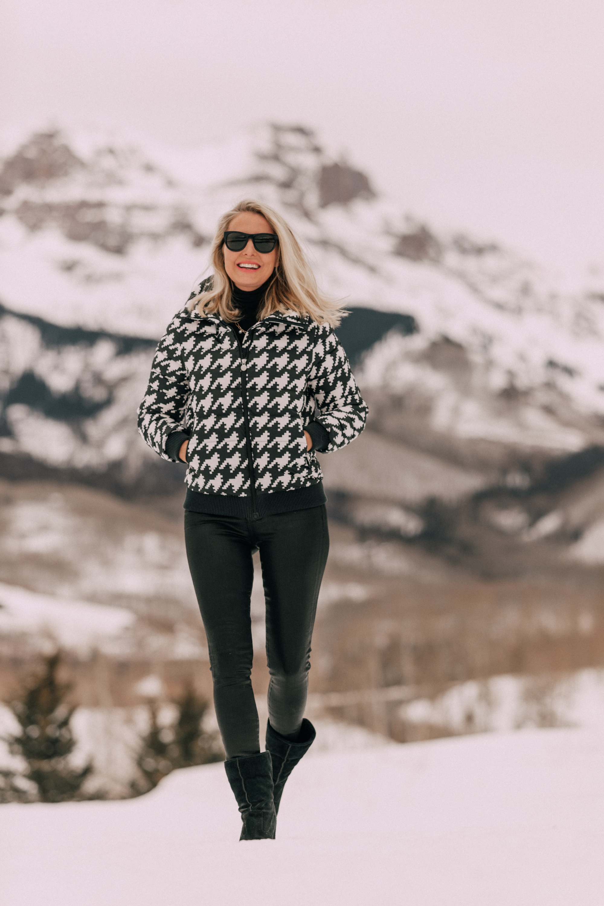 Chic Ski Brand, Fashion blogger Erin Busbee of BusbeeStyle.com wearing black Rocket leatherette Skinny Jeans by Citizens of Humanity with a black cashmere turtleneck sweater by Aqua, and a houndstooth puffer jacket by Perfect Moment from Shopbop, and Ugg wedge boots in the snow in Telluride, CO