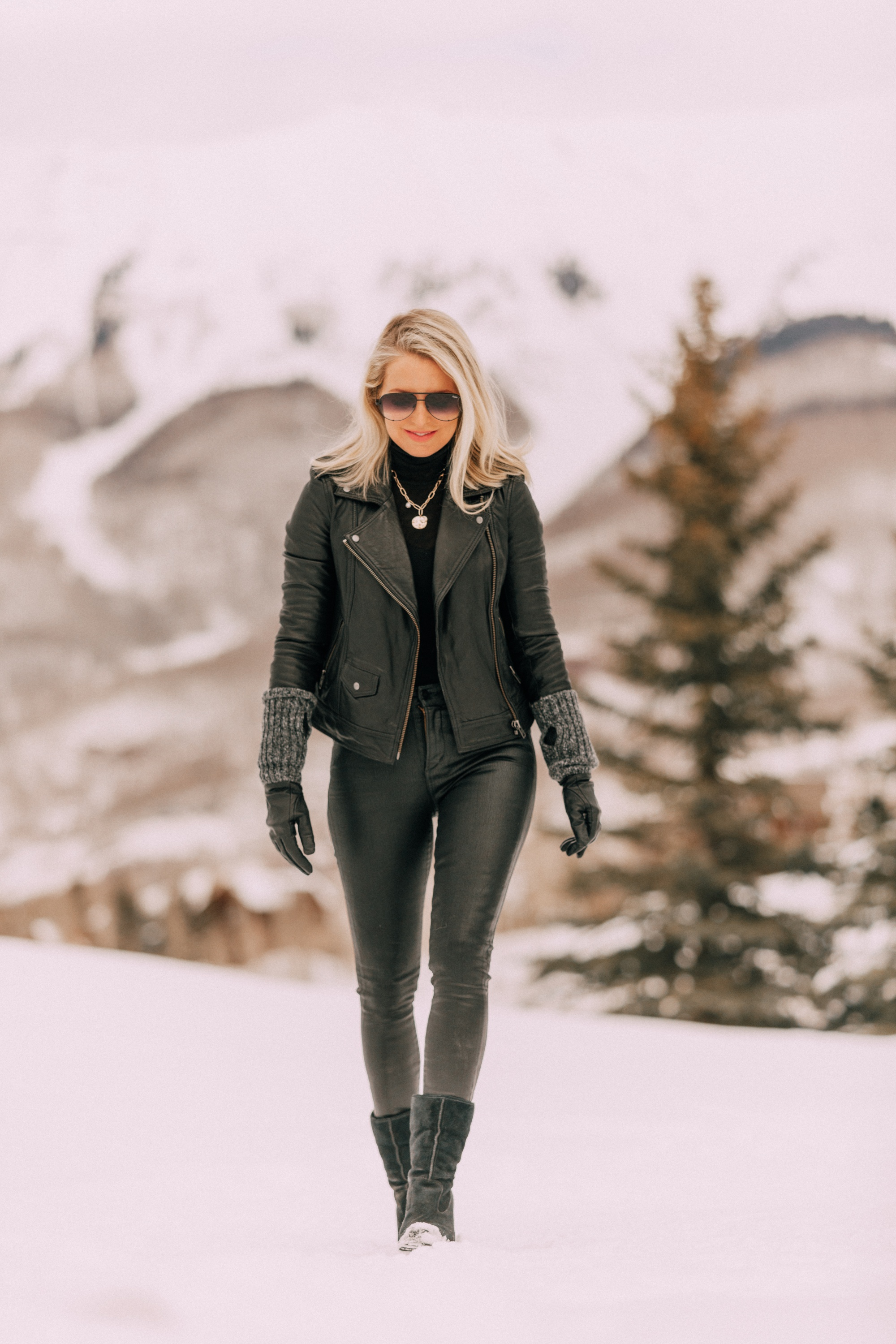 How To Layer A Moto Jacket, Fashion blogger Erin Busbee of BusbeeStyle.com wearing a black leather IRO moto jacket, Carolina Amato gloves, rocket leatherette skinny jeans by Citizens of Humanity, black cashmere turtleneck, and Ugg wedge boots in Telluride, CO