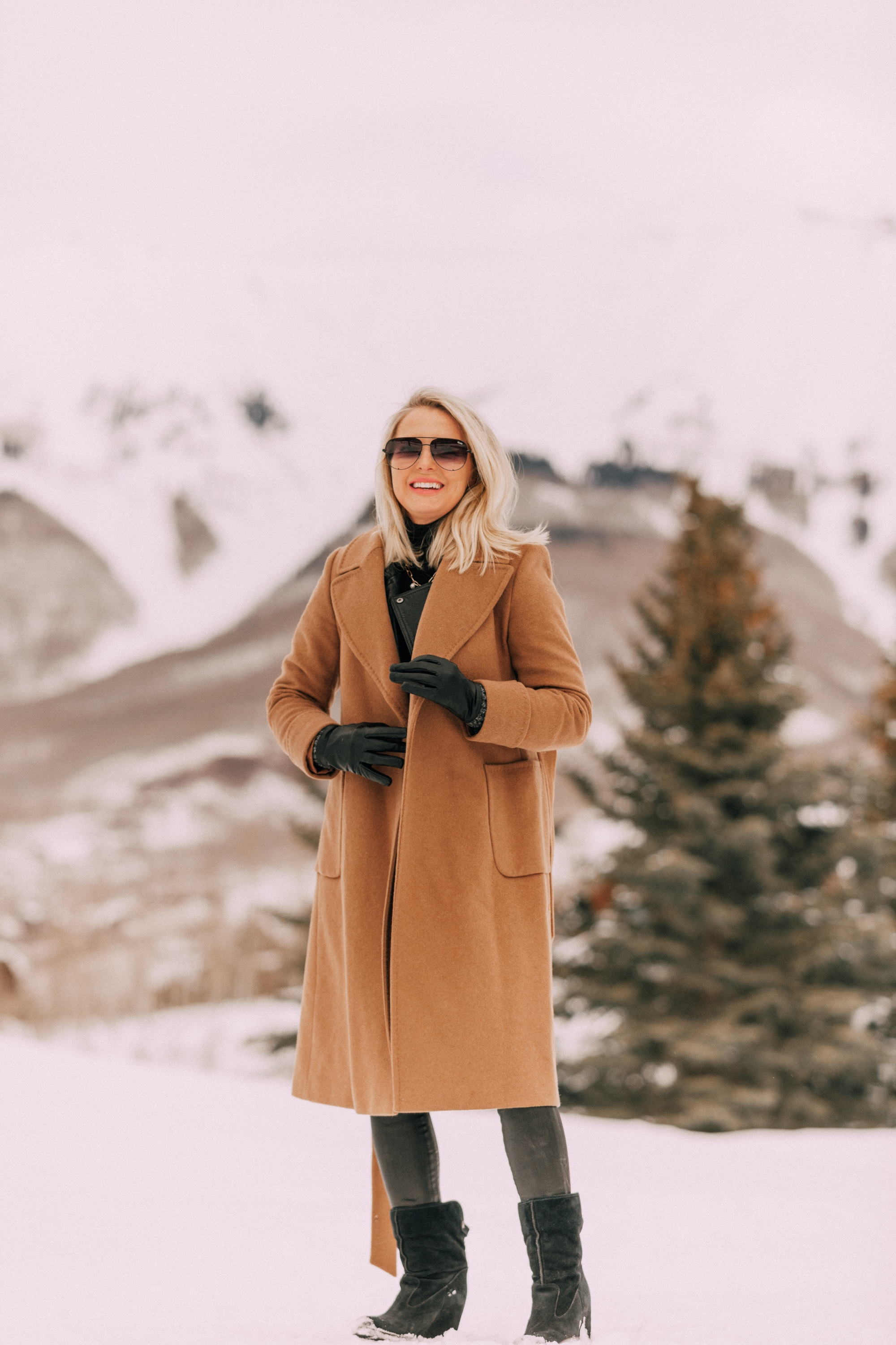 How To Layer A Moto Jacket, Fashion blogger Erin Busbee of BusbeeStyle.com wearing a black leather IRO moto jacket, Carolina Amato gloves, rocket leatherette skinny jeans by Citizens of Humanity, black cashmere turtleneck, and Ugg wedge boots and putting on a wool camel coat by Mackage in Telluride, CO