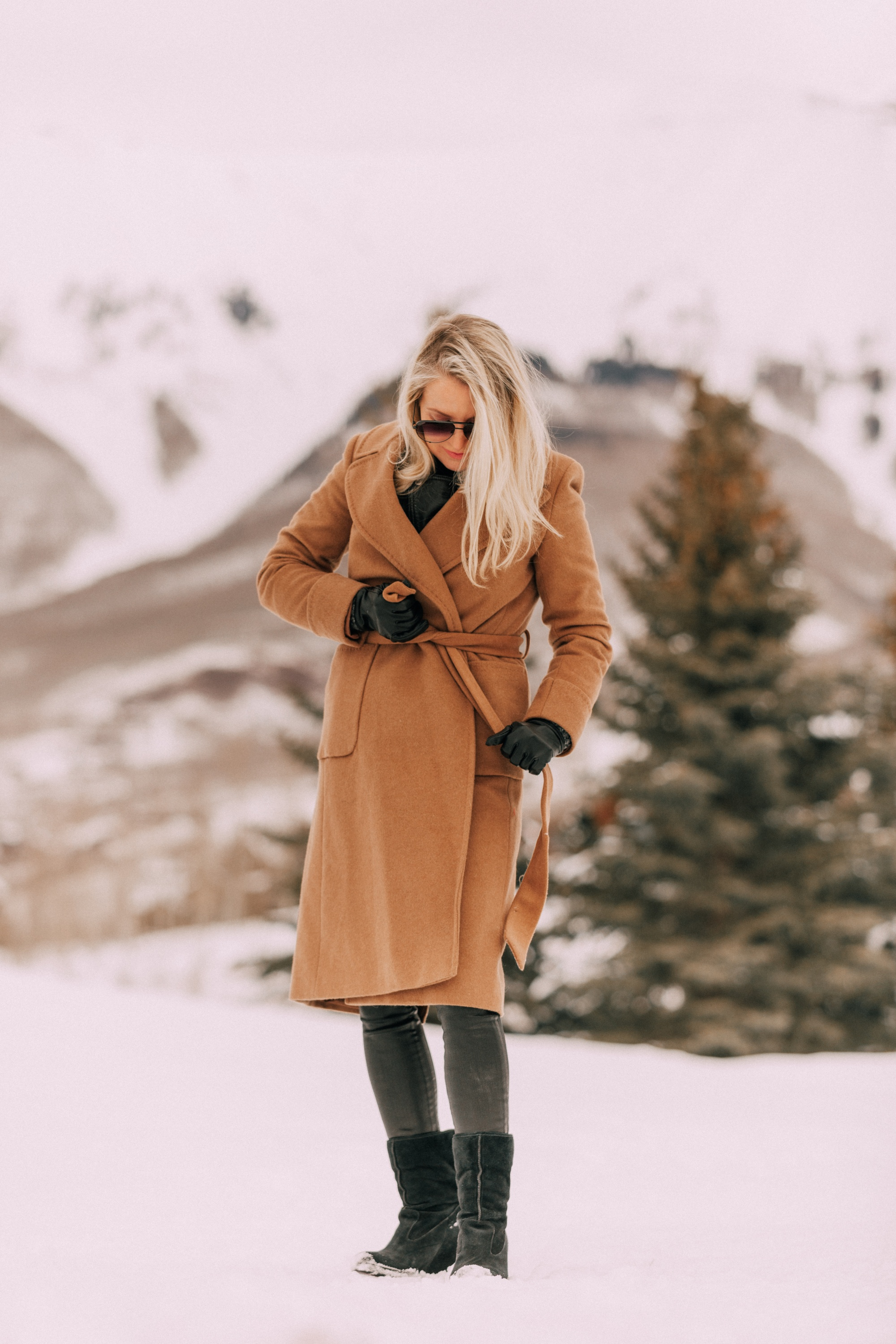 How To Layer A Moto Jacket, Fashion blogger wearing a black leather IRO moto jacket underneath Mackage long camel coat Carolina Amato gloves, rocket leatherette skinny jeans by Citizens of Humanity, black cashmere turtleneck, and Ugg wedge boots in Telluride, CO