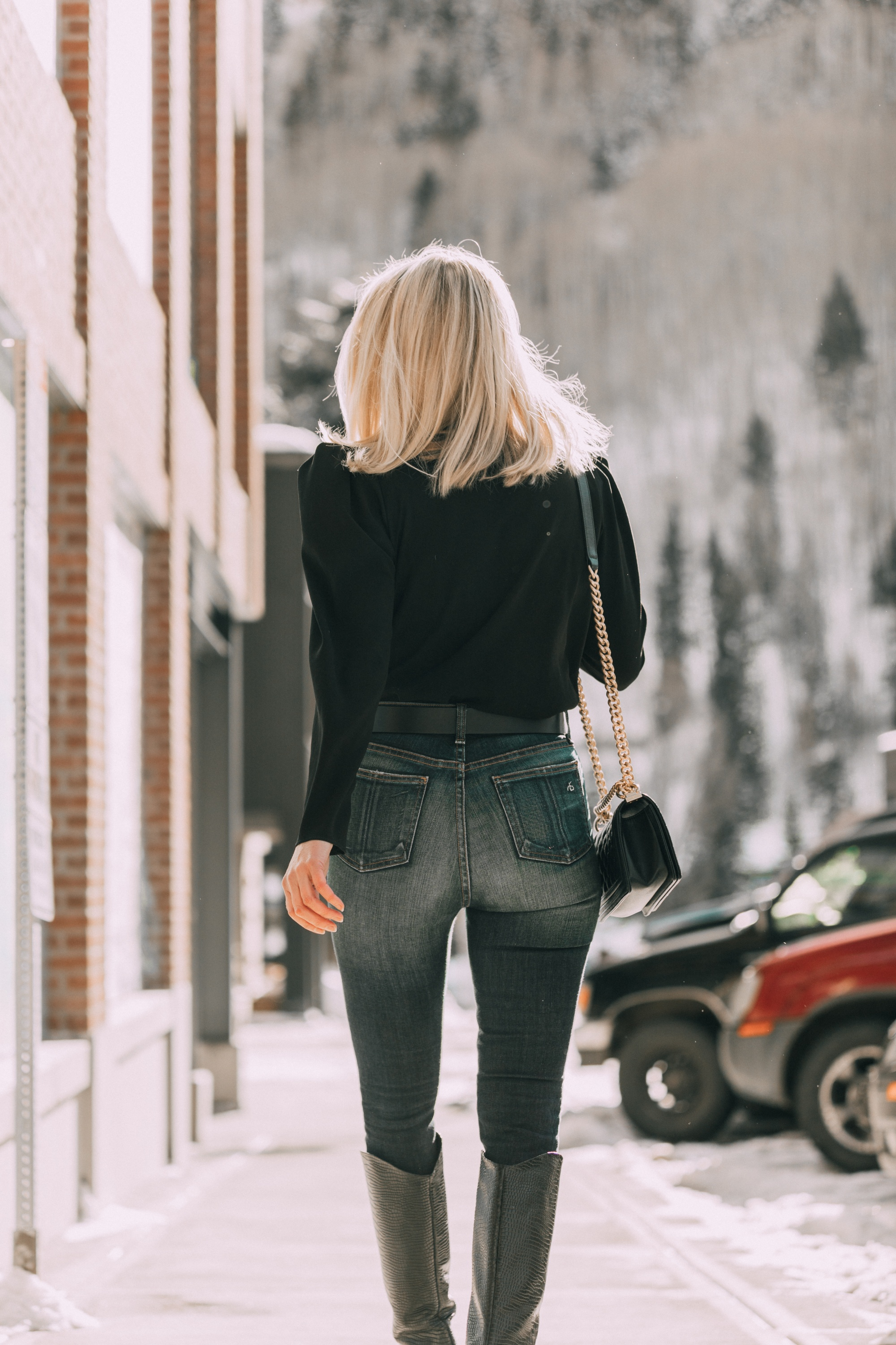 Date Night Outfits, Fashion blogger Erin Busbee of BusbeeStyle.com wearing a black puff sleeve blouse by IRO, ripped skinny jeans by Rag & Bone, Schutz black croc-embossed knee high boots, Chanel boy bag, and Topshop belt in Telluride, Colorado