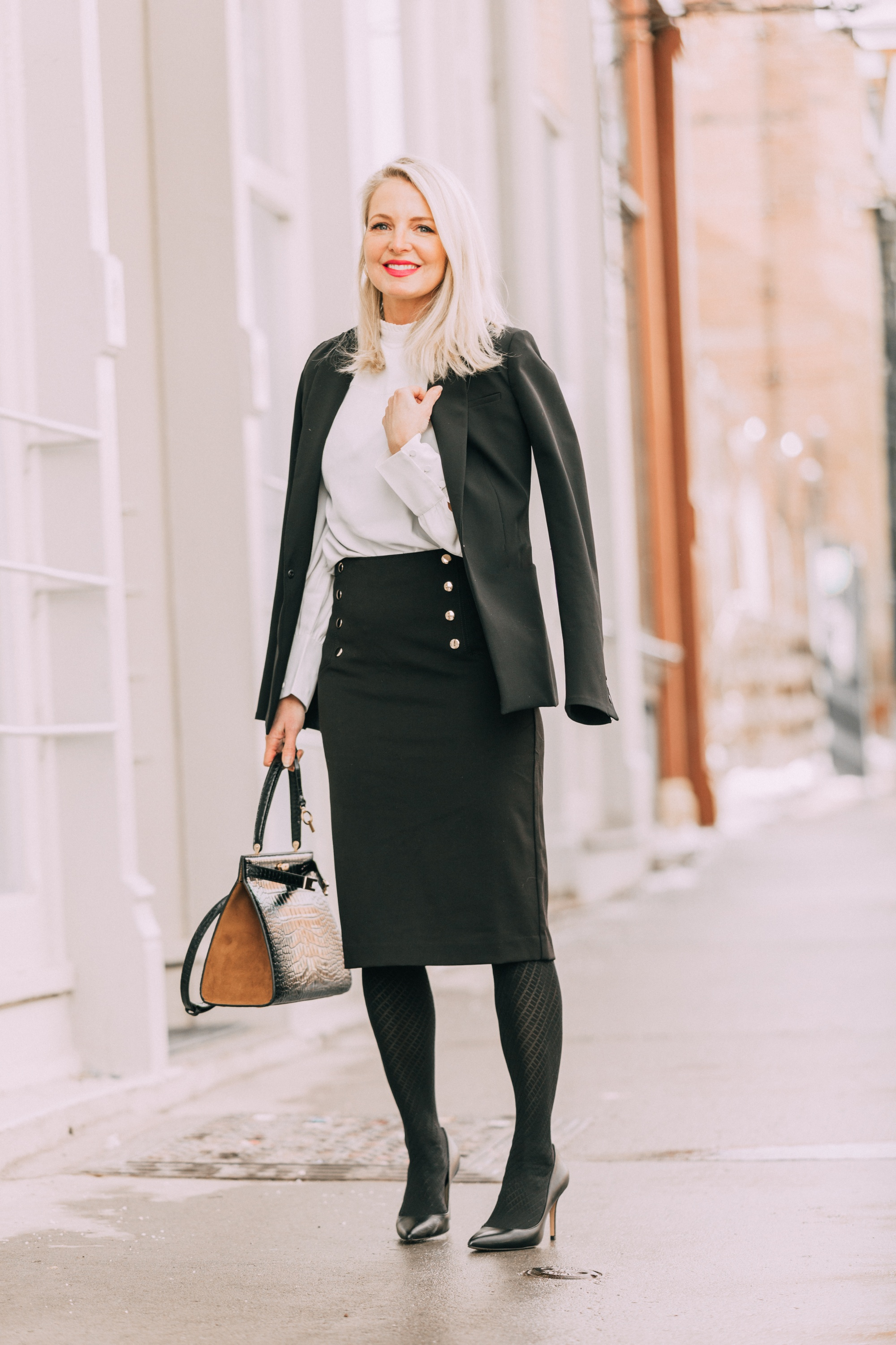 Wardrobe Basics, Fashion blogger Erin Busbee of BusbeeStyle.com sharing wardrobe basics from Ann Taylor wearing a black pencil skirt with sailir buttons, a white ruffle neck blouse, classic black blazer, black tights, and black pumps all from Ann Taylor in Telluride, Colorado