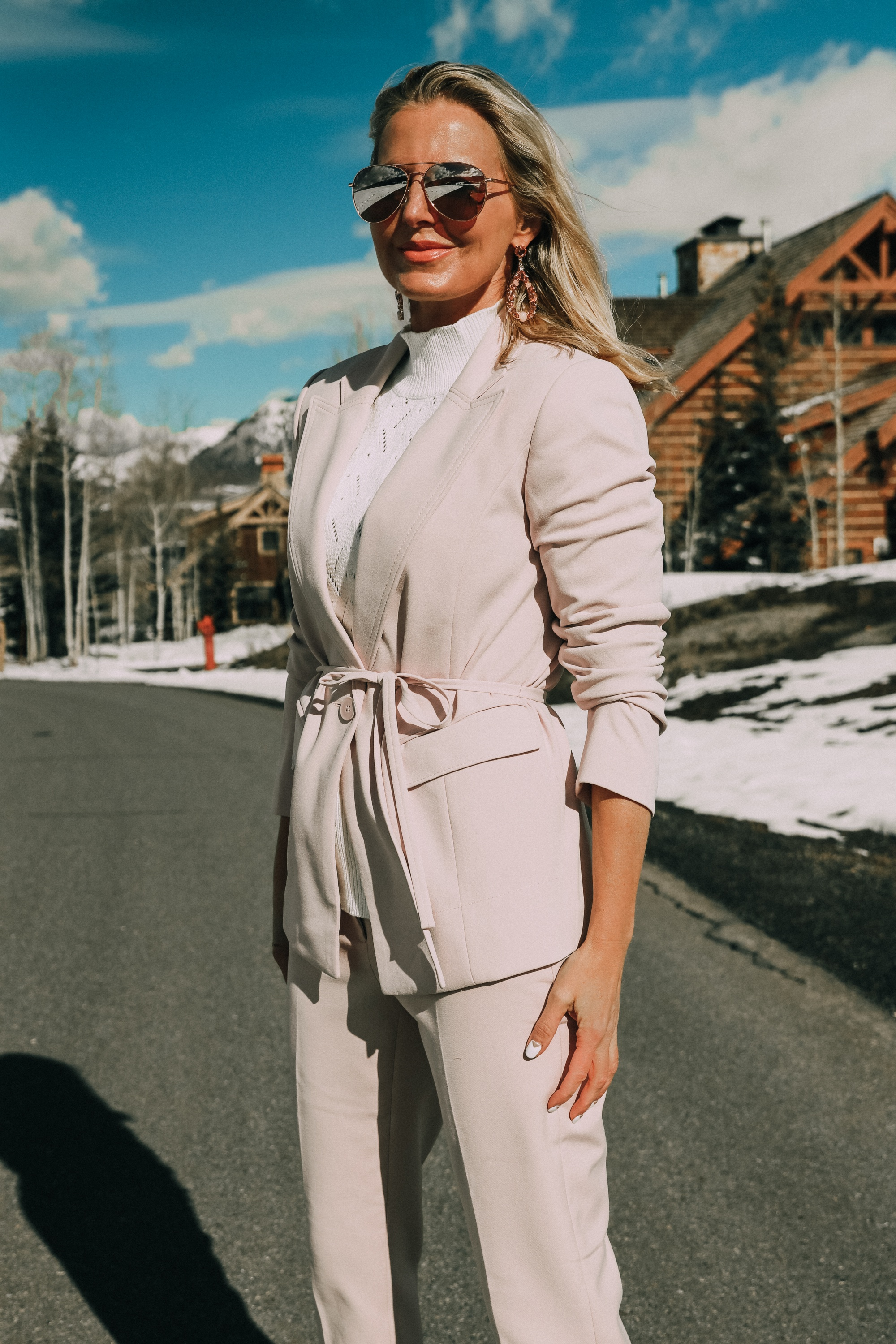 Pink Office Outfit, Fashion blogger Erin Busbee of BusbeeStyle.com wearing a pink power suit from White House Black Market, including a pink belted blazer, pink soft stretch pants, white puff sleeve sweater dress, pink pumps, pink earrings, and aviator sunglasses in Telluride, Colorado