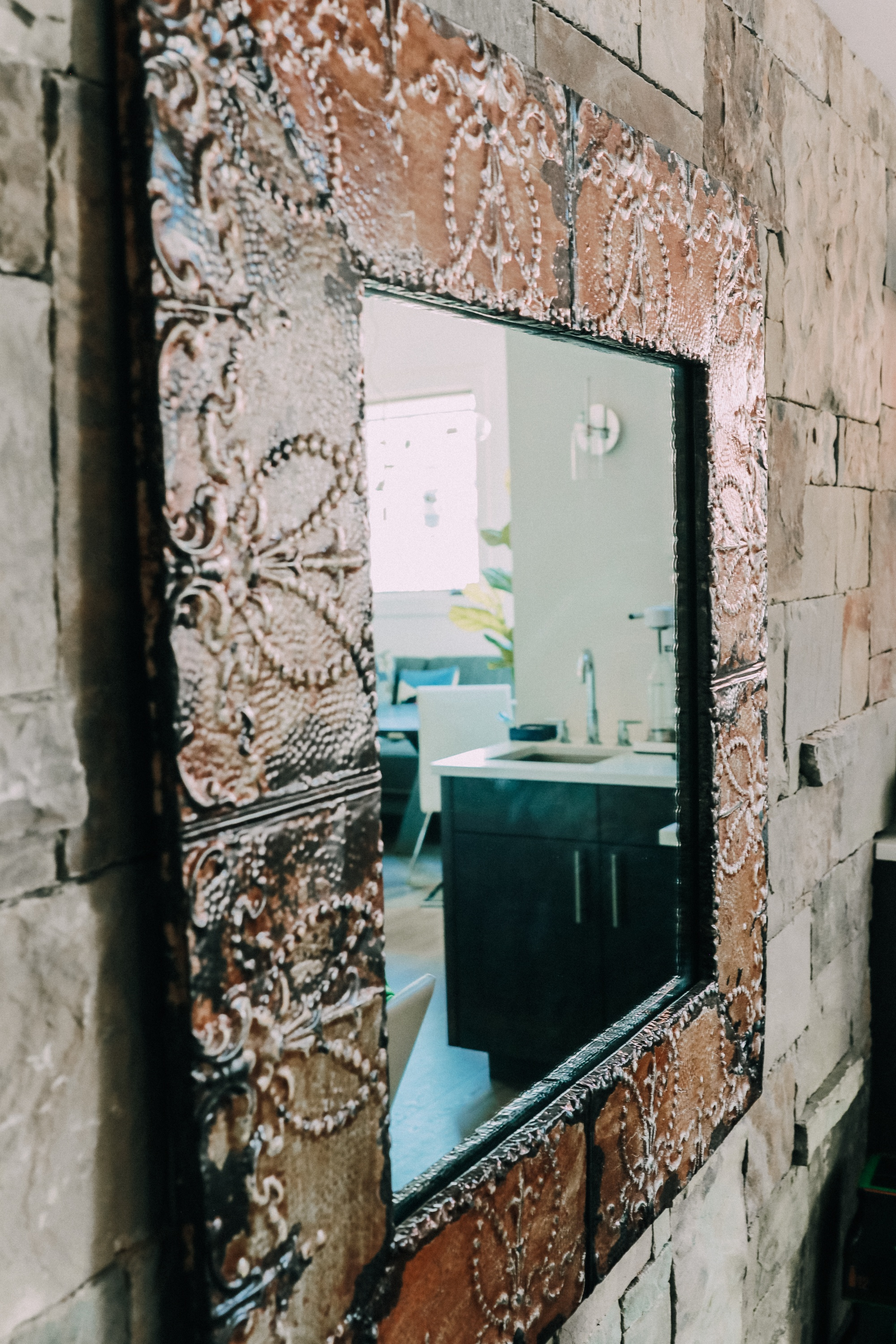 tin wall mirror hanging on a stone wall, interior home mirrors, home decor