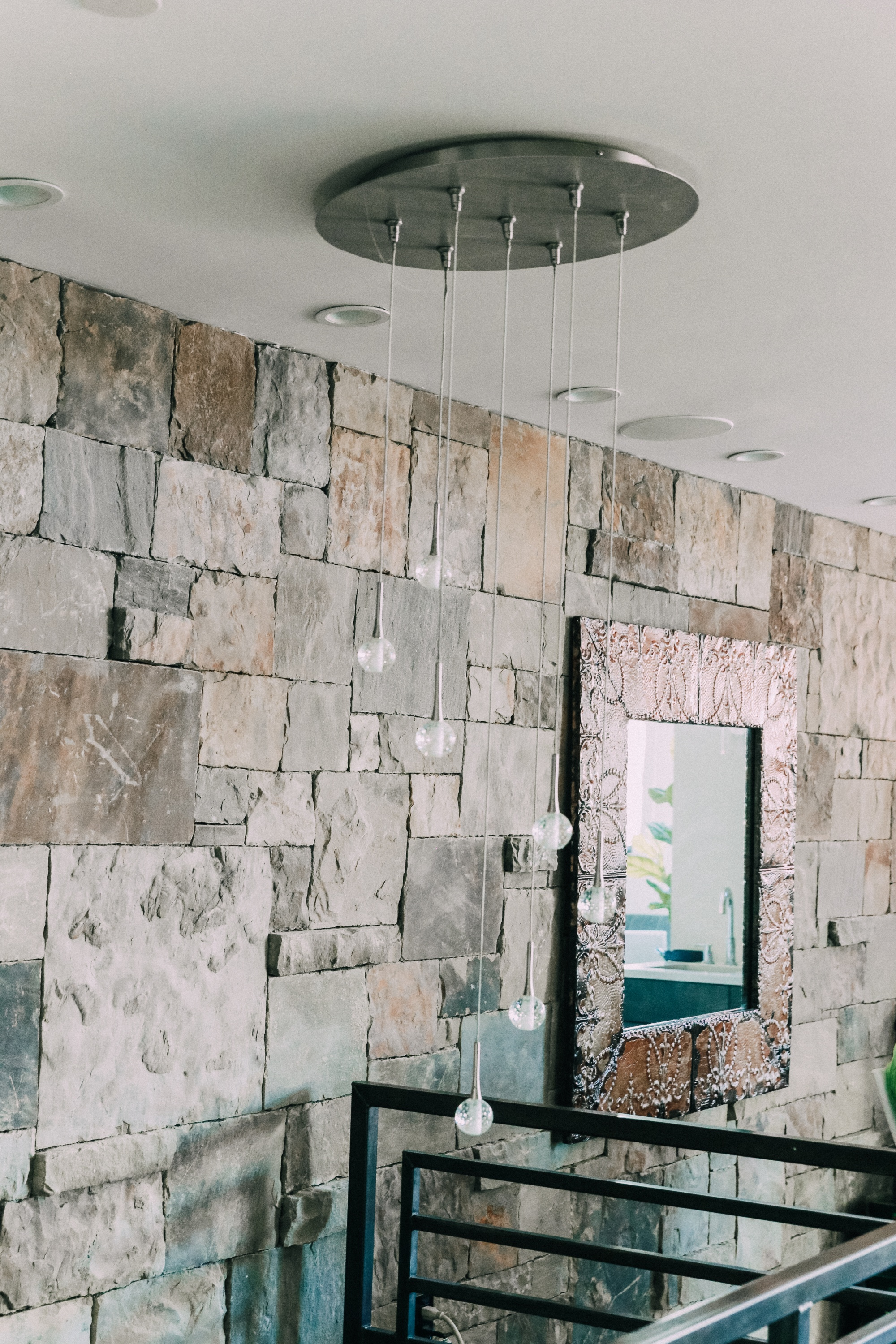 tin mirror hanging on a stone wall cascading chandelier over staircase