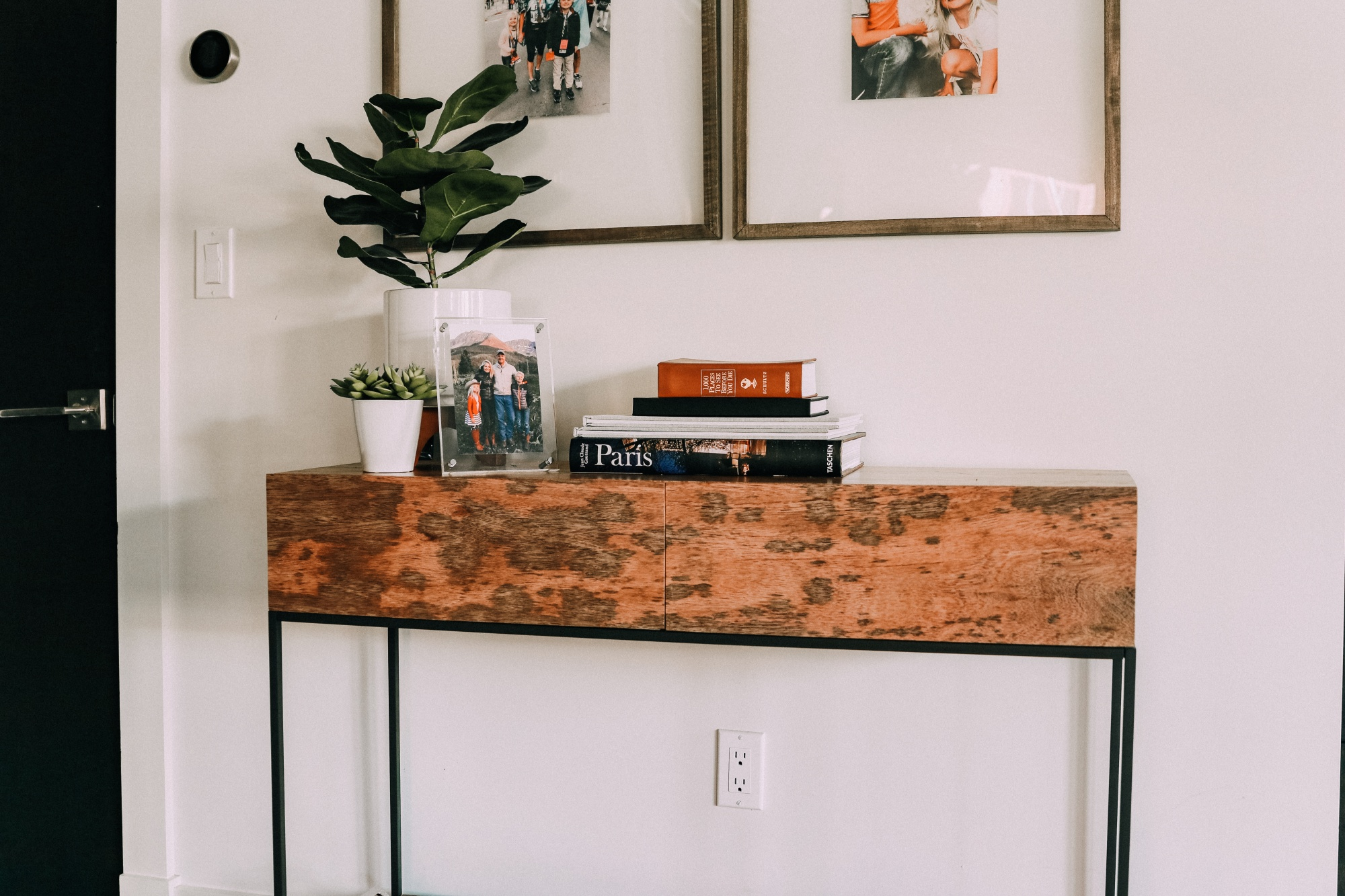 burl wood console table with framed family photos master bedroom decor