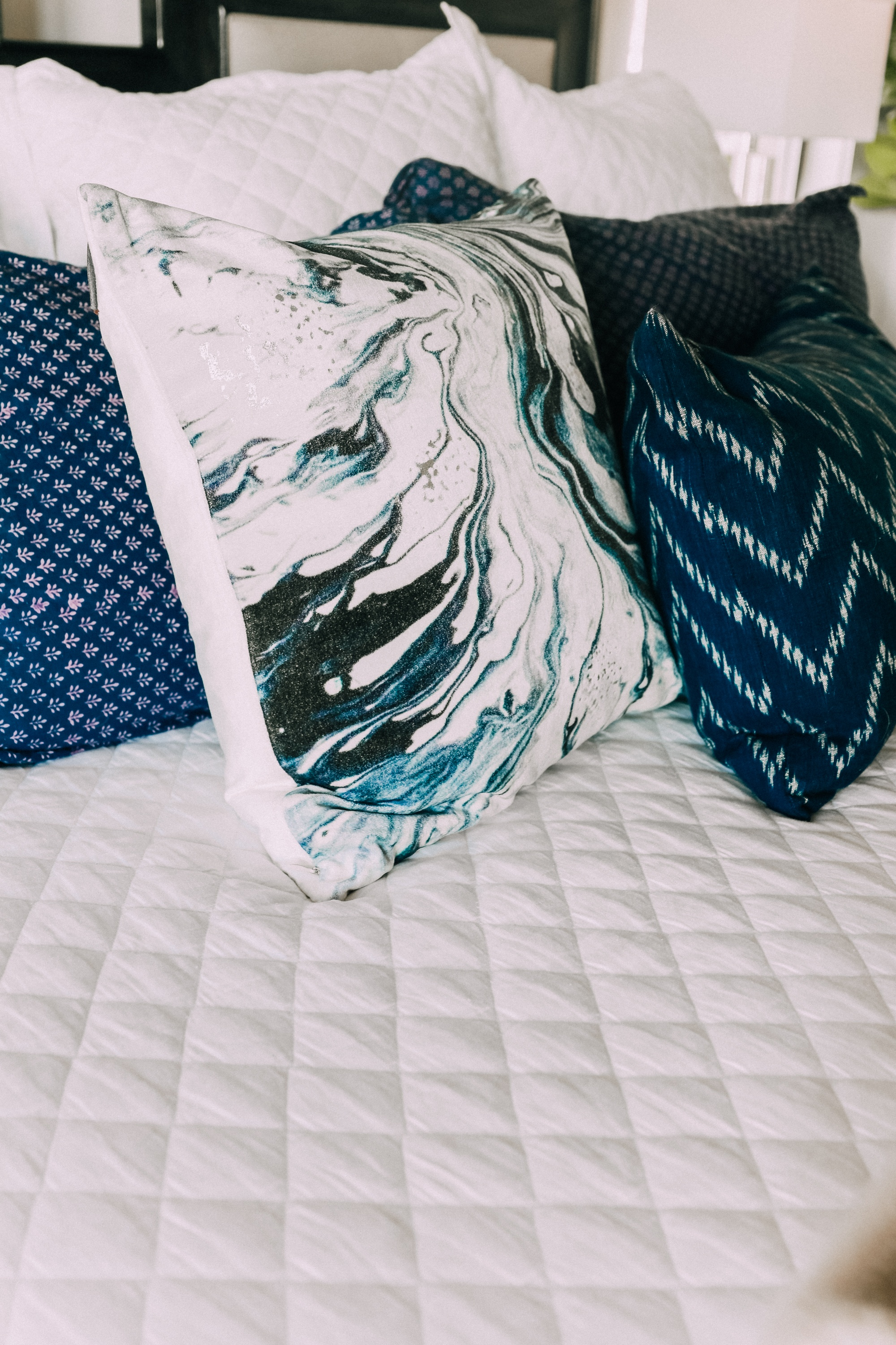 master bedroom blue and white throw pillows on white bedspread