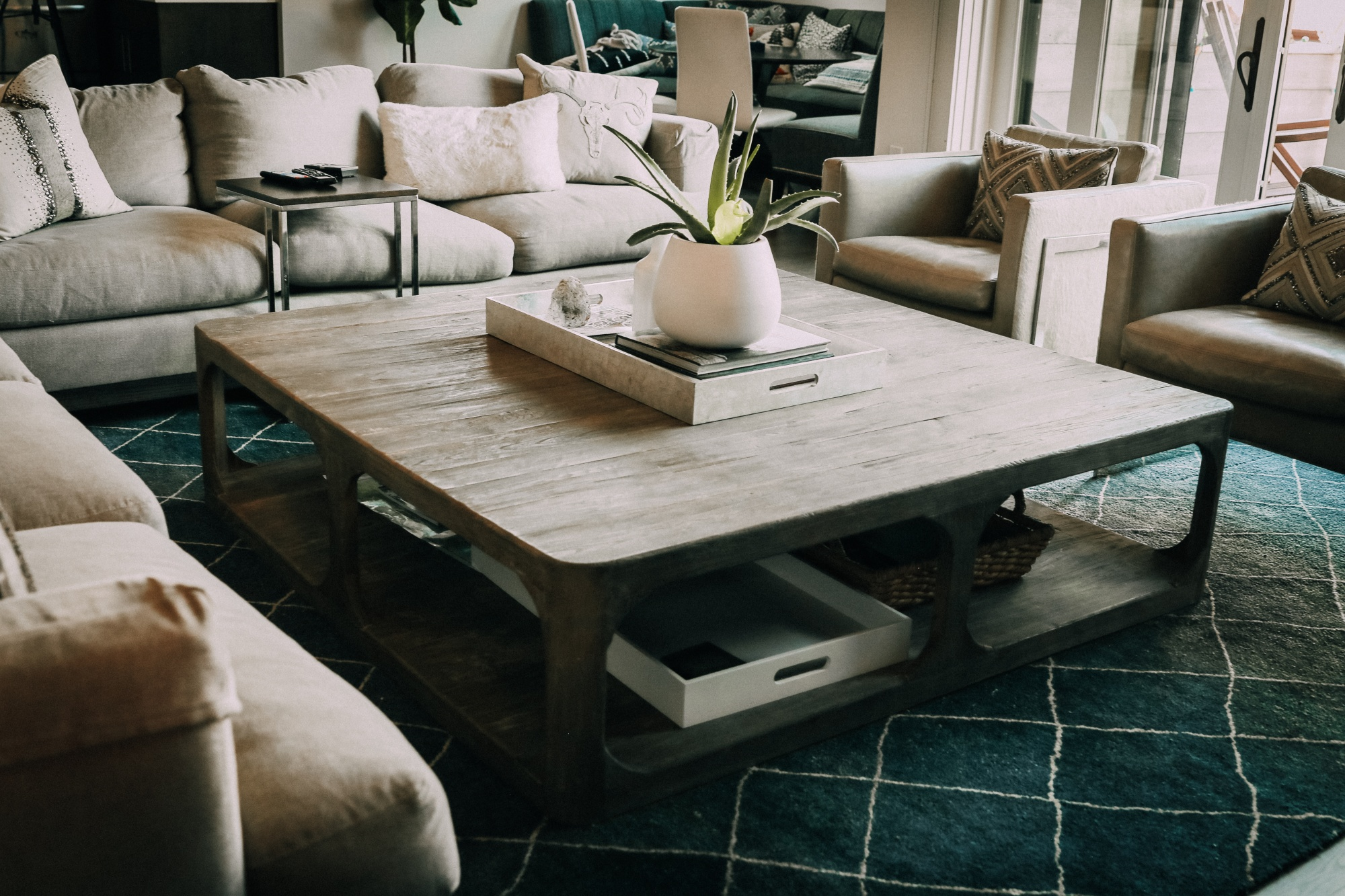 linen sofas, large gray wood coffee table, white vases from west elm, and gray leather club chairs from restoration hardware with cloud9 designs pillows