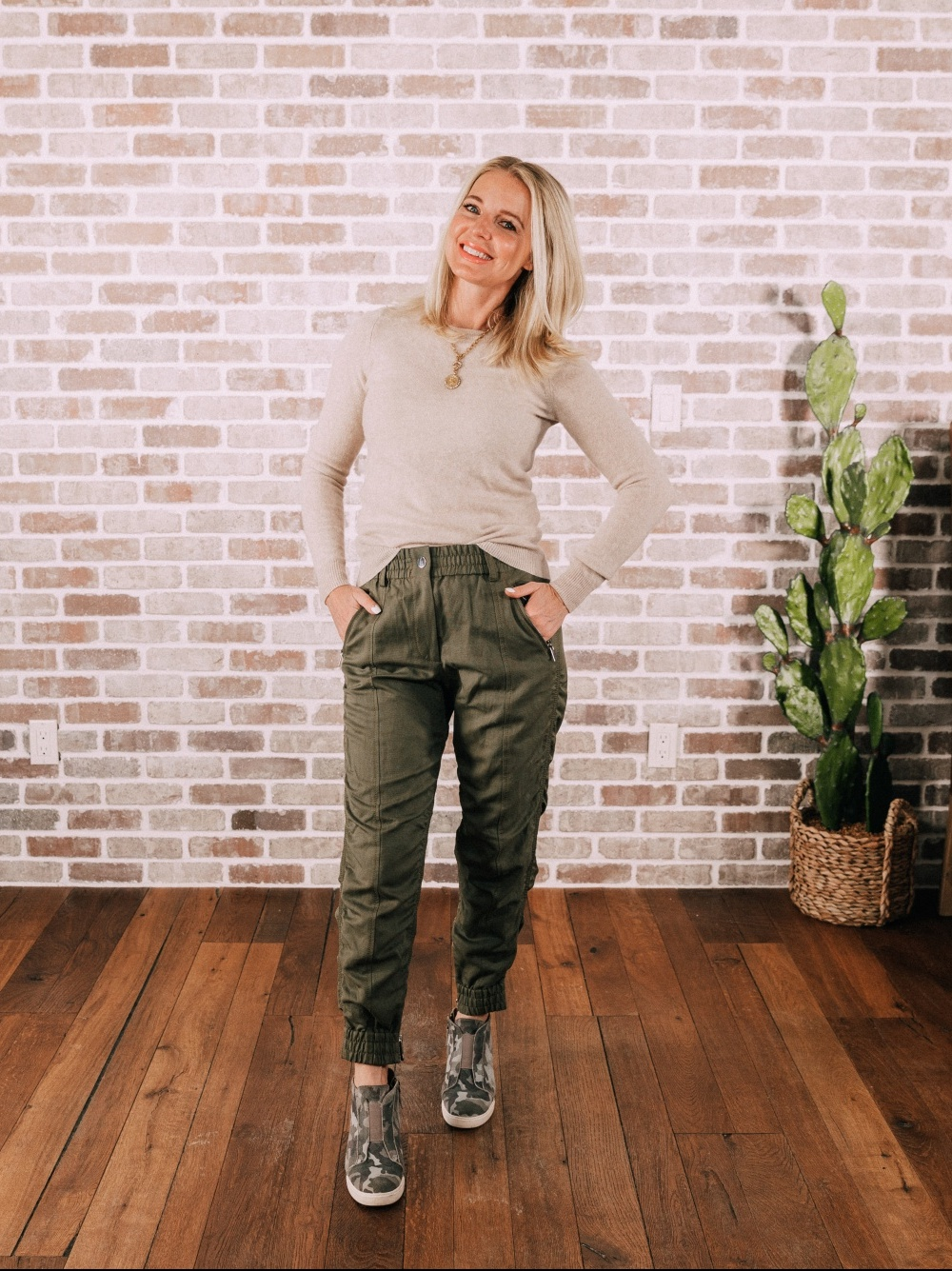 Stylish Work From Home Outfits, Fashion blogger Erin Busbee of BusbeeStyle.com wearing a beige cashmere sweater with Derek Lam green joggers and camo Linea Paolo wedge sneakers in Telluride, Colorado