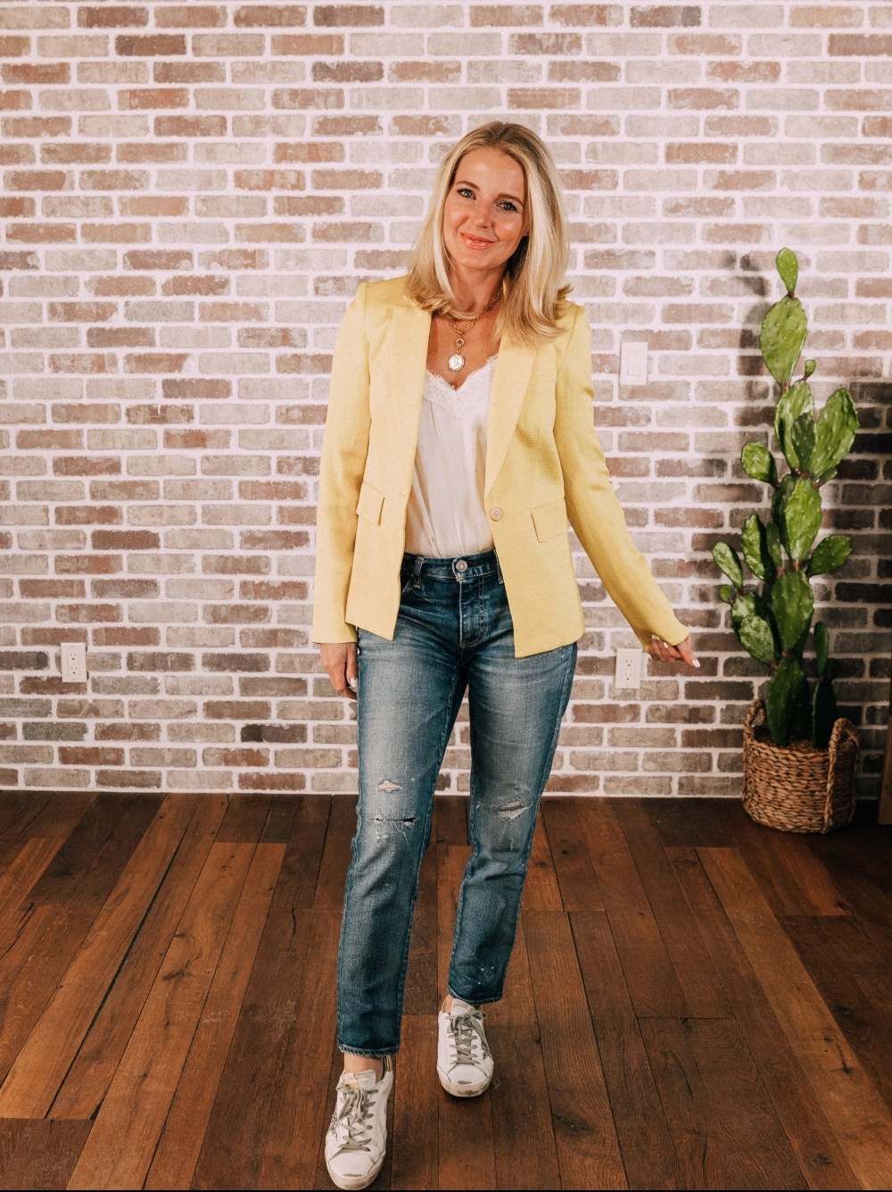 Stylish Work From Home Outfits, Fashion blogger Erin Busbee of BusbeeStyle.com wearing a yellow blazer by Veronica Beard with white cami, Moussy Vintage jeans, and golden goose sneakers in Telluride, Colorado