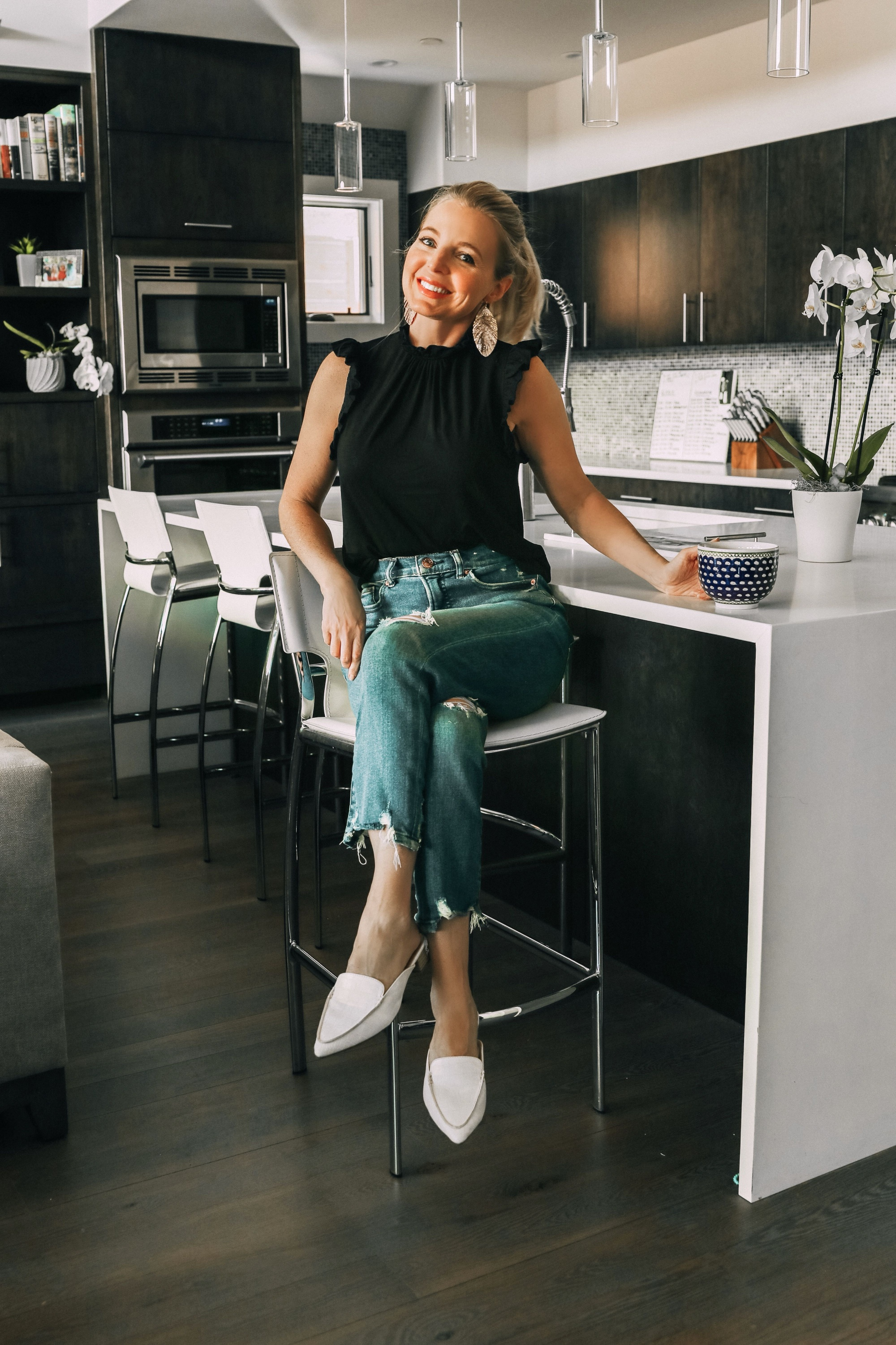 Work from home outfits that are affordable from Express featuring high rise distressed mom jeans, white loafers, black mock neck ruffle cotton top and lightweight leaf earrings