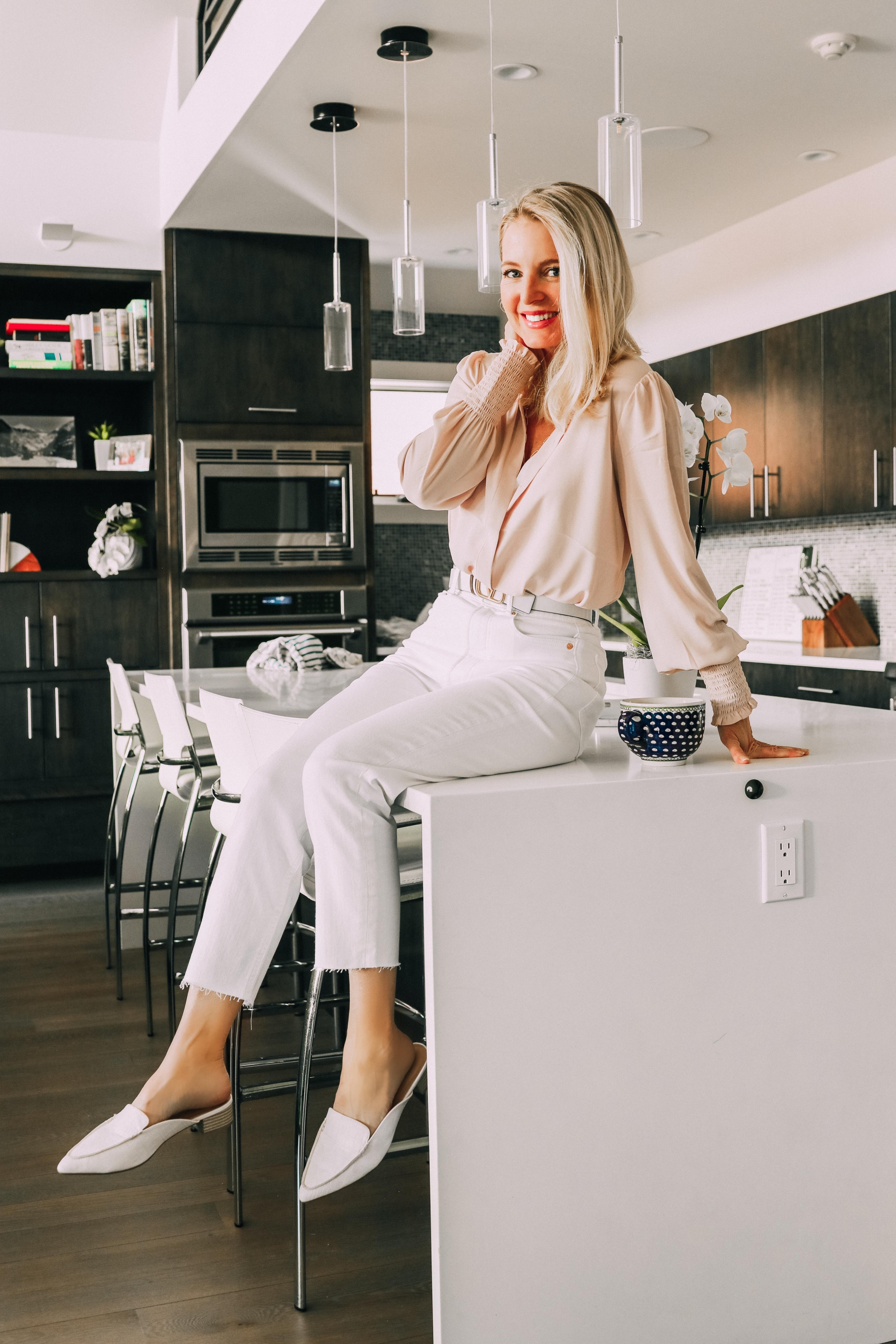 white cropped mom jeans for women over 40, Work from home outfit with pale pink button-down blouse, valentino belt and white mock croc slide loafers