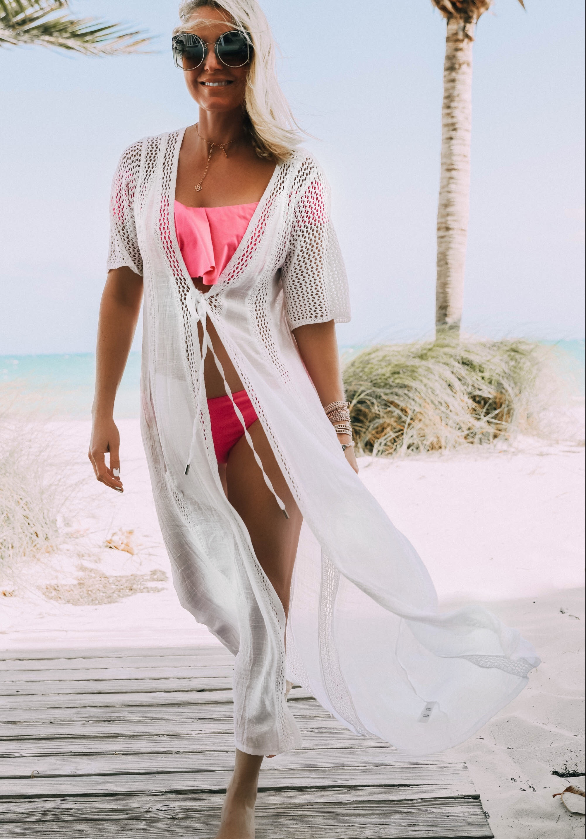 Fashion blogger wearing white crochet swimsuit coverup by Elan over pink bikini bathing suit in the Bahamas