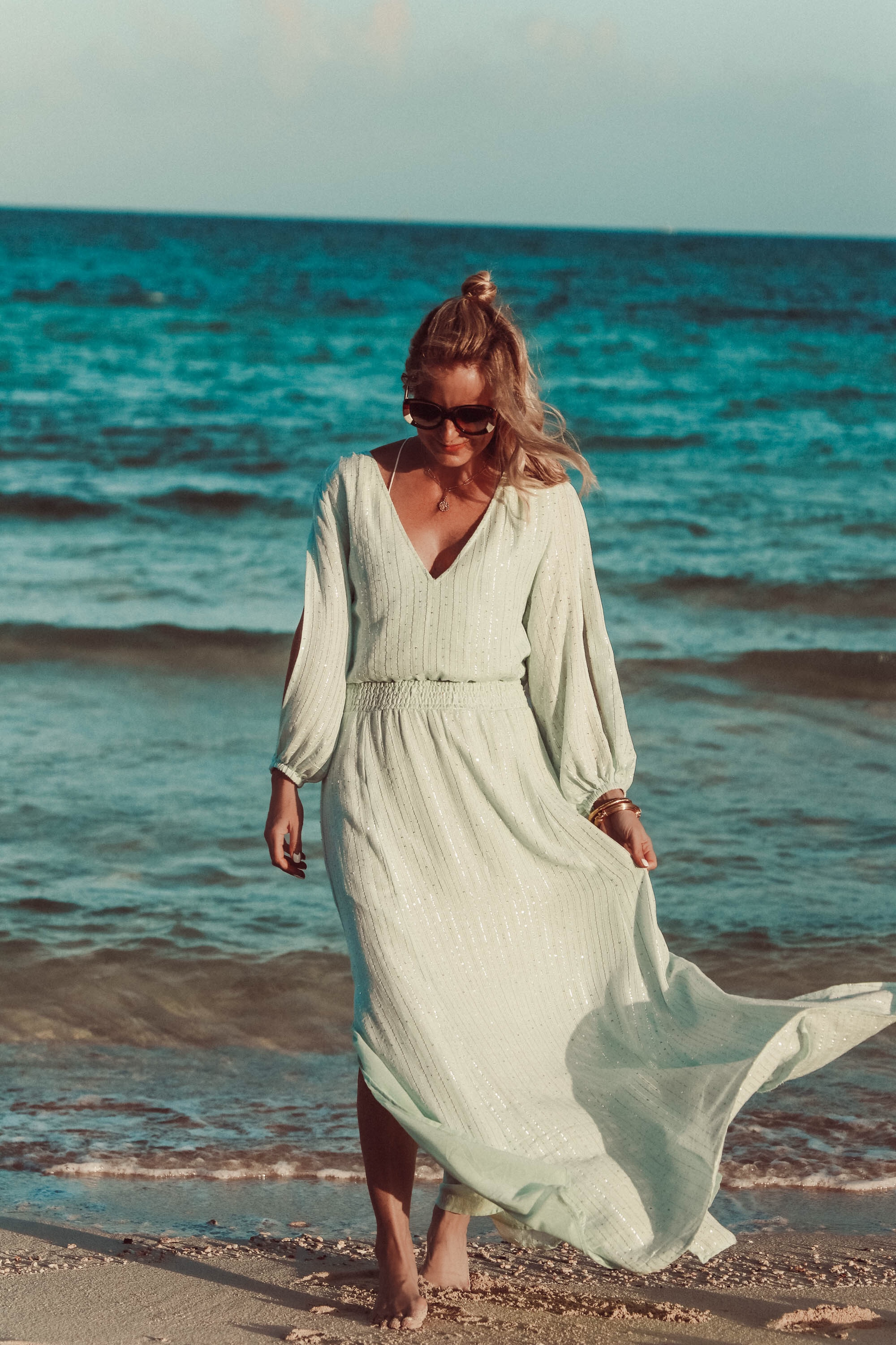 Maxi Dresses For Summer, Fashion blogger Erin Busbee of Busbee Style wearing a blue sequin maxi dress by Sundress, Chloe brown rainbow sunglasses, and Aligheri gold ritual necklace walking on the beach in the Bahamas,